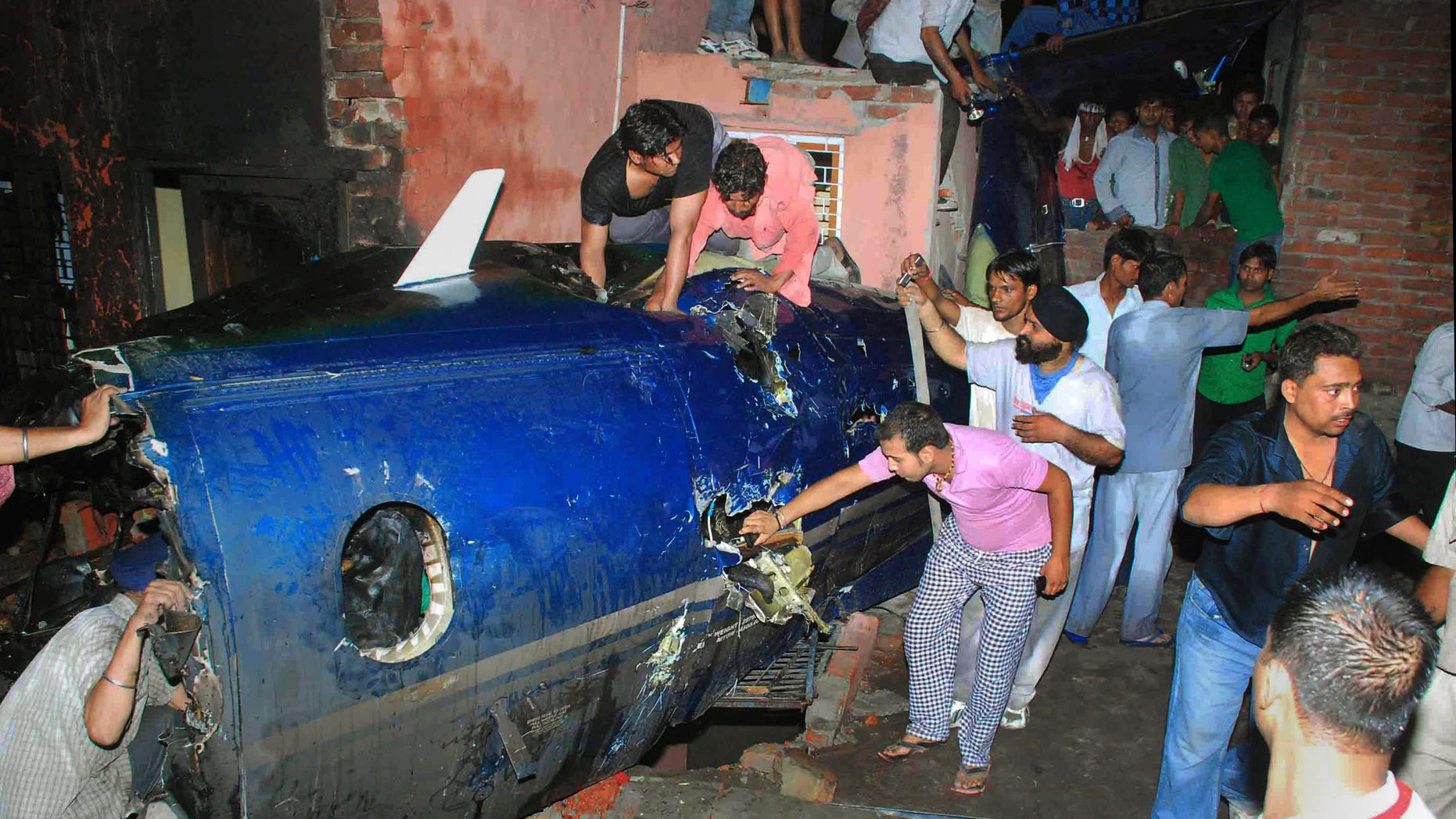 May 25: Indian residents search around the wreckage of a small plane after it crashed into a residential community in Faridabad, near New Delhi, India. A government official says the crash of a small chartered plane in a residential area on the outskirts of the Indian capital has killed at least 10 people and injured another two. (AP)