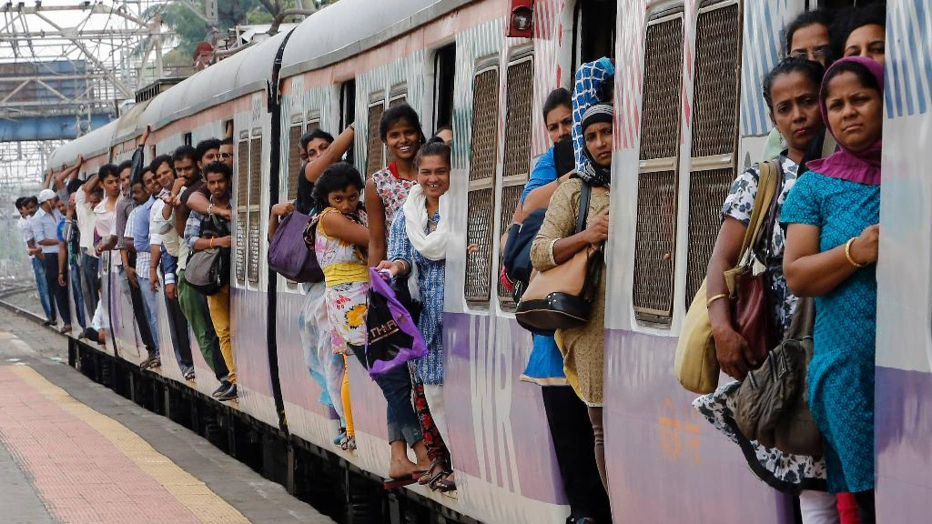 Commuters hang by doors of a crowded local train in Mumbai, India, Tuesday, July 8, 2014. India's new rail minister Sadananda Gowda on Tuesday proposed allowing foreign investment to modernize the country's cash-strapped state railways. India has one of the world's largest railways, which transports 23 million passengers a day. Indian Railways is one of the world's biggest employers with more than 1.3 million employees. The network lost 300 billion rupees ($5 billion) last year. (AP Photo/Rajanish Kakade)