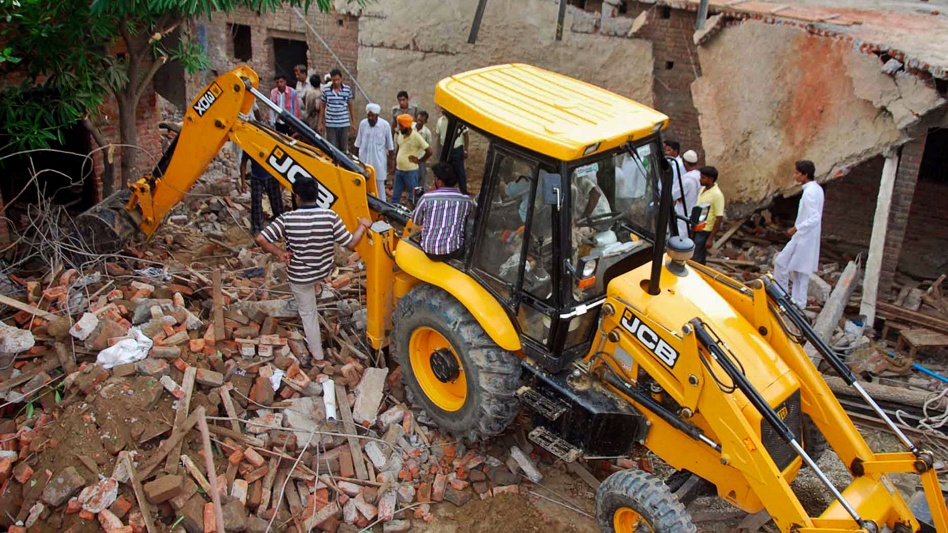 July 27, 2012- Indian rescue workers try to clean the debris after a school roof collapsed in Bijnore 185 miles southwest of state capital Lucknow, India.