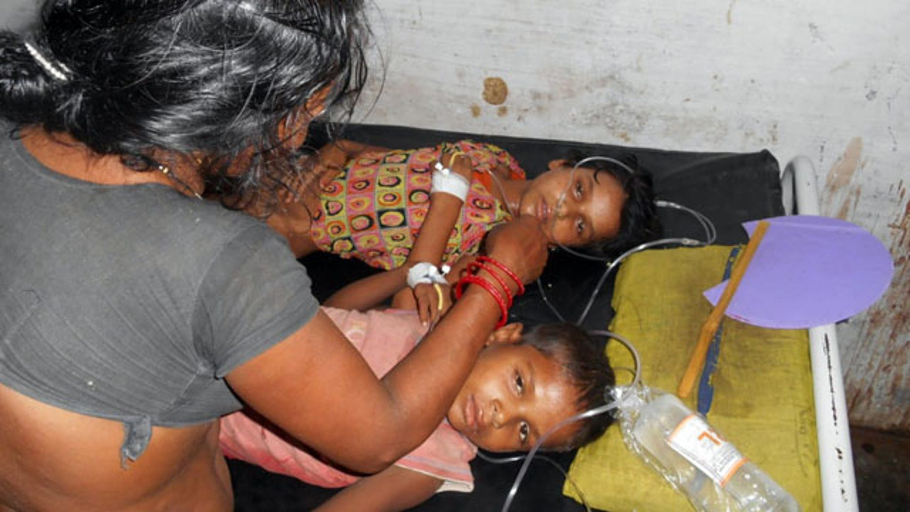 July 16, 2013:  Schoolchildren receive treatment at a hospital after falling ill soon after eating a free meal at a primary school in Chhapra district, in the eastern Indian state of Bihar. (AP Photo)