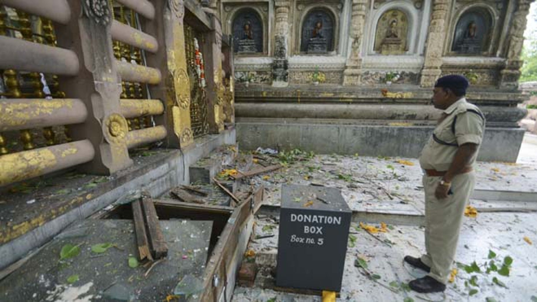 July 7, 2013: A security officer inspects the site of an explosion on the campus of the Mahabodhi Temple, the Buddhist Great Awakening temple, in Bodhgaya, about 130 kilometers (80 miles) south of Patna, the capital of the eastern Indian state of Bihar. A series of small blasts hit three Buddhist temples in eastern India early Sunday, injuring at least two people, police said.