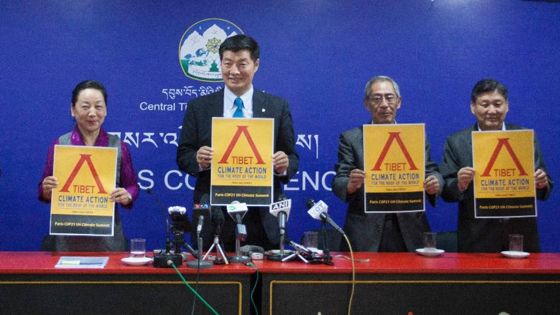Prime minister of the Tibetan government in exile, Lobsang Sangay, center flanked by government officials unveils the Tibet Climate Action poster during the launch of a campaign in Dharamsala, India, Tuesday, Oct. 20, 2015. The Dalai Lama on Tuesday urged the world's nations to take strong action to limit global warming and to protect fragile environments including the Himalayan glaciers and Tibetan plateau.(AP Photo/Shailesh Bhatnagar)