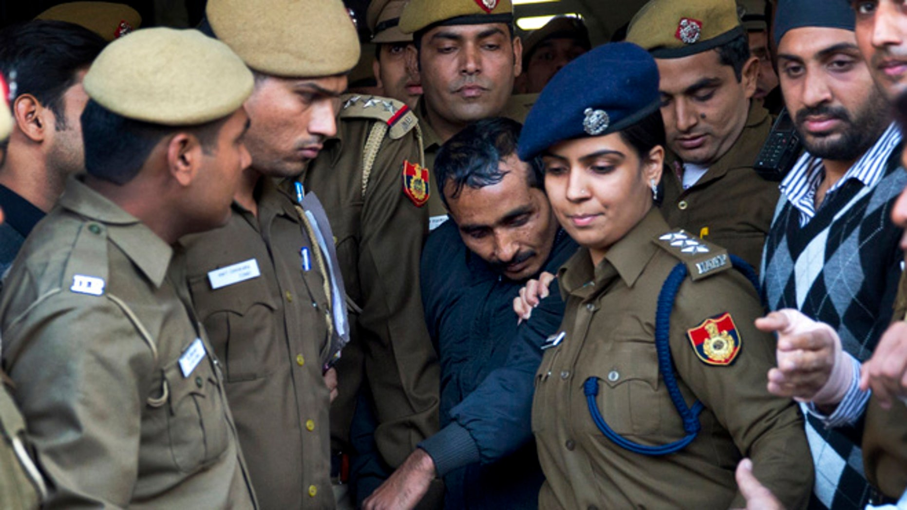 Dec. 8, 2014: Shiv Kumar Yadav, center, a driver from the international taxi-booking service Uber, is surrounded by police as he is brought out after being produced in a court in New Delhi, India.