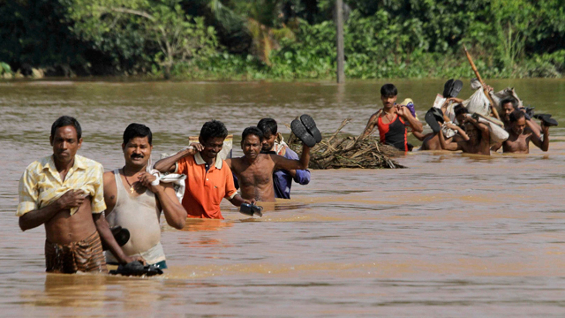 Sept. 28: Villagers ford floodwaters at Patamundi near Kendrapara, about 75 miles north of Bhubaneshwar, India.