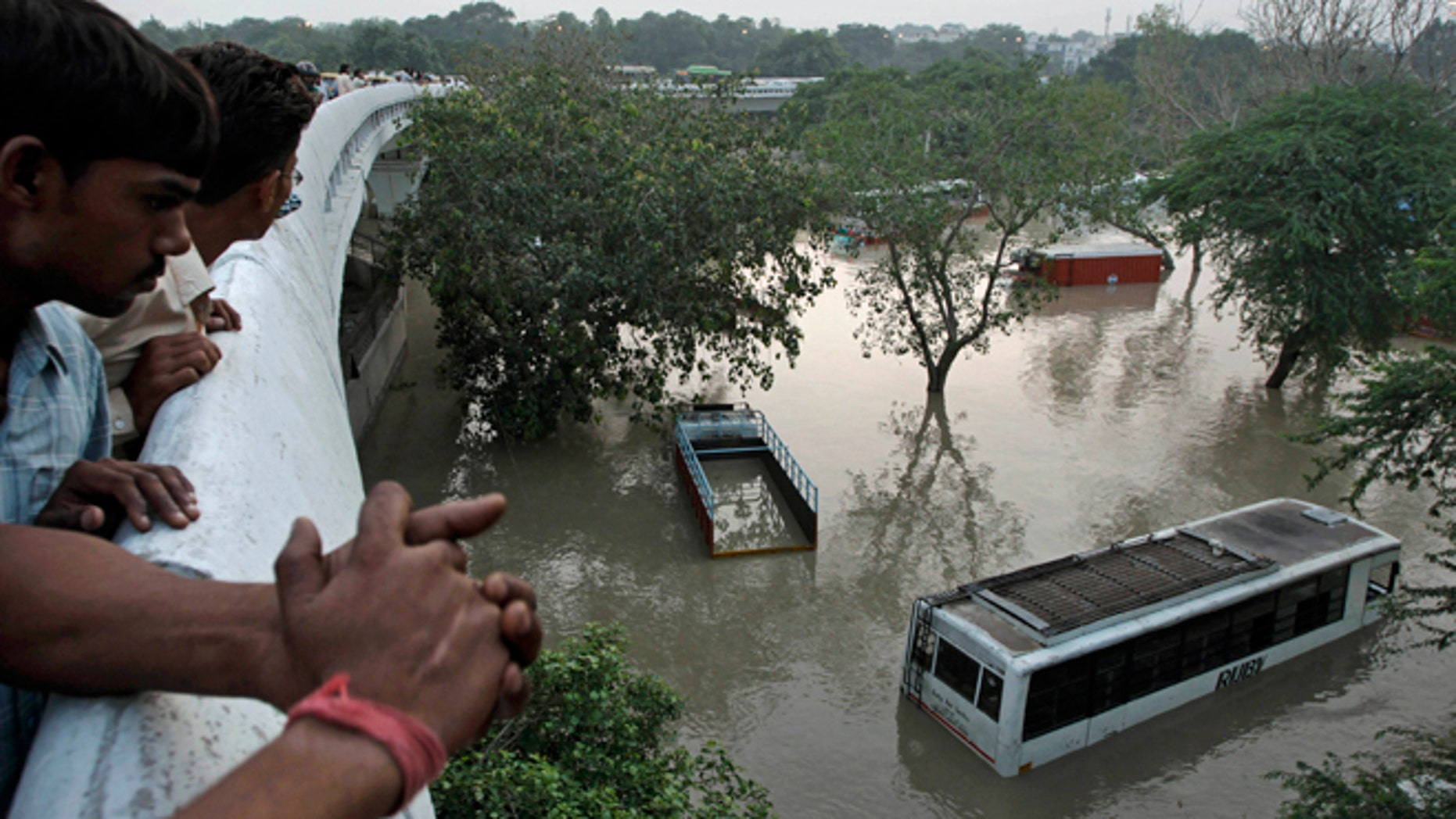 June 19, 2013: People gather to look at submerged buses and trucks in the rising Yamuna River as they stand on a flyover in New Delhi, India. Indias prime minister said Wednesday that the death toll from flooding this week in the northern state of Uttrakhand had surpassed 100 and could rise substantially.