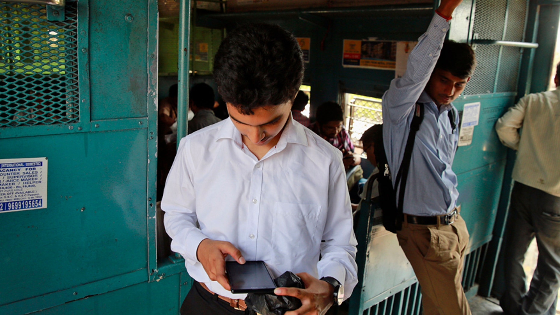 An Indian man surfs the internet on his smartphone as he travels in a local train in Mumbai, India, Tuesday, March 24, 2015.