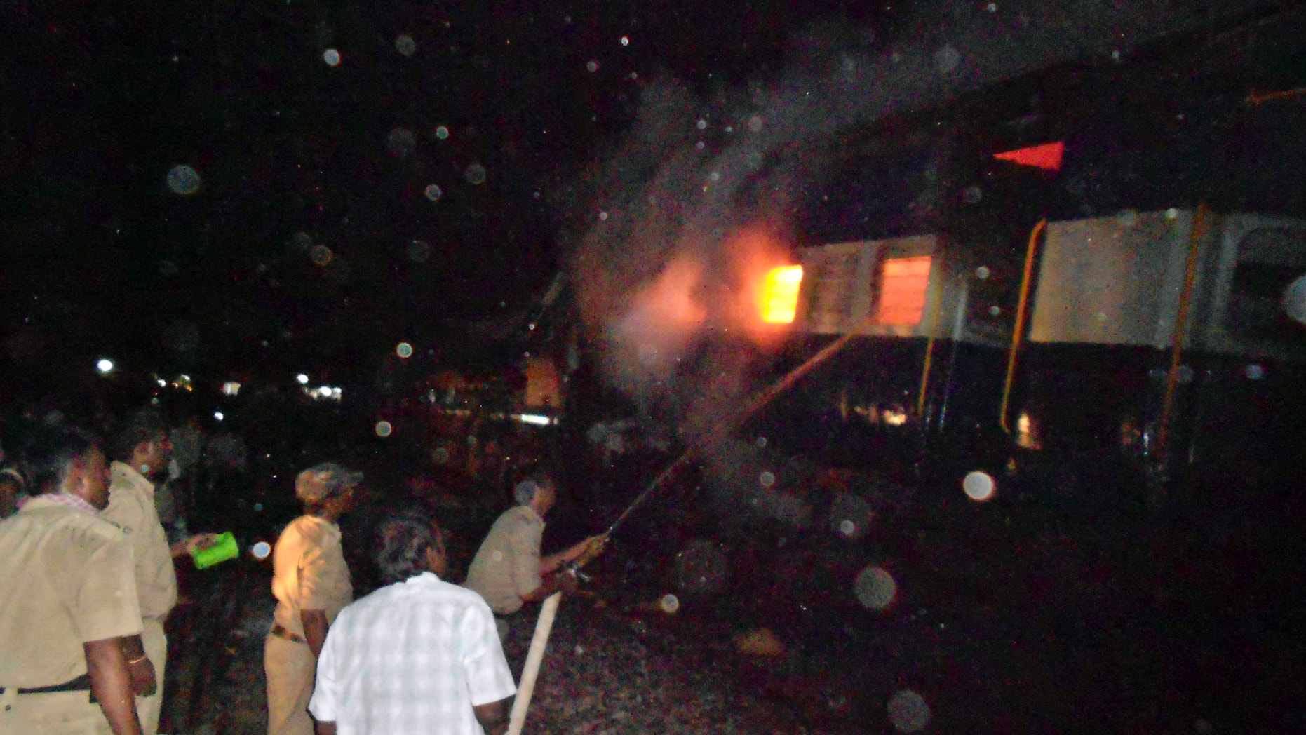 May 22, 2012: Firefighters and policemen try to douse flames on a train after an accident at a station near Penukonda.
