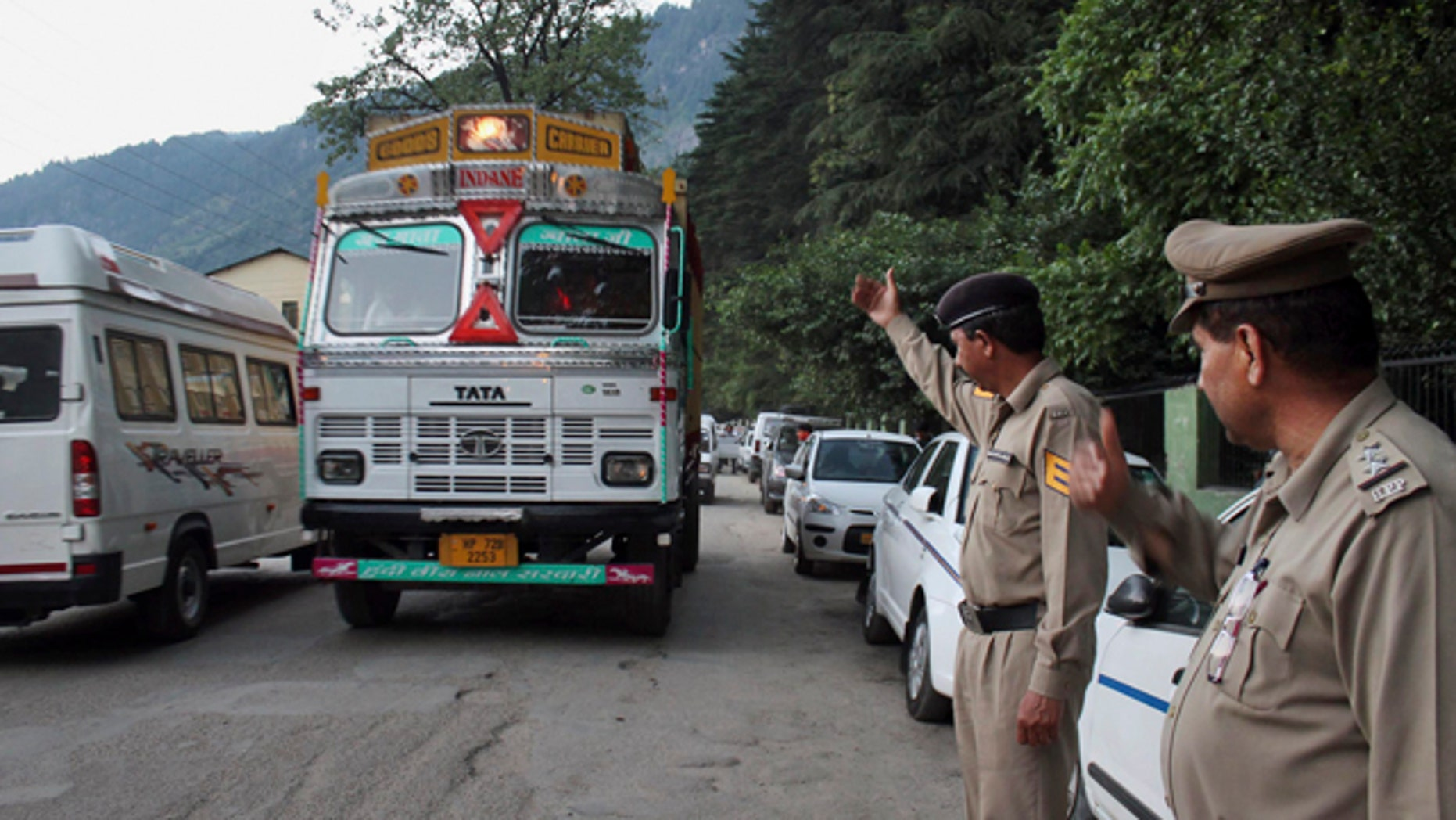 June 4, 2013: Indian policemen keep a check on vehicles after an American woman was gang-raped Tuesday in the northern Indian resort town of Manali, India.