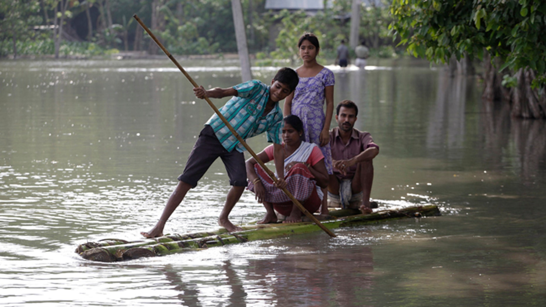 Sept. 22: A boy rows his family across floodwaters on a banana raft in Lachi Bishnupur village.