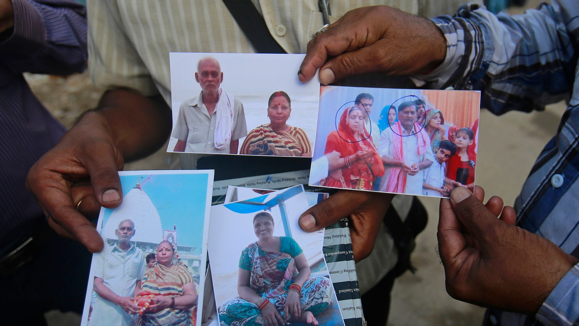 Relatives of missing people, affected by the flash floods and landslides, display their photographs outside the Indian Air Force base in Dehradun, in the Himalayan state of Uttarakhand June 26, 2013.