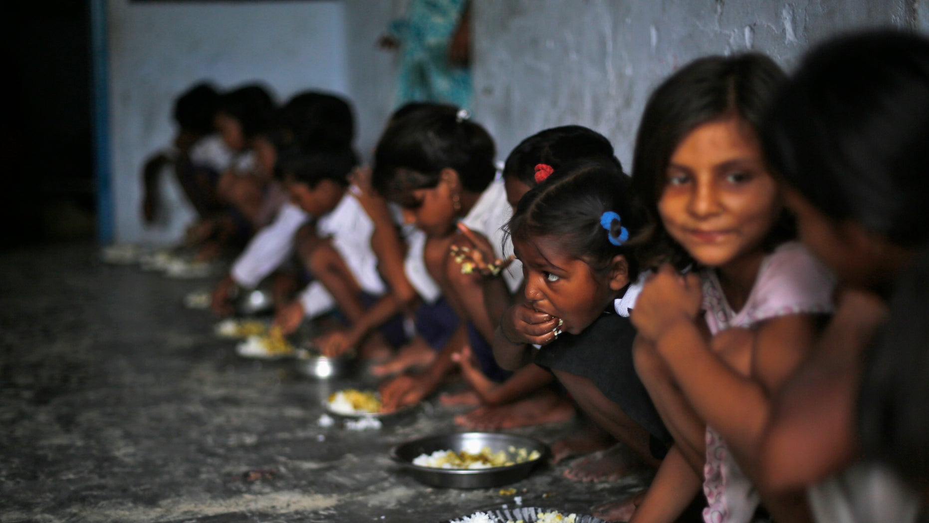 School children eat their free mid-day meal, distributed by a government-run primary school in  the eastern Indian state of Bihar July 19, 2013.