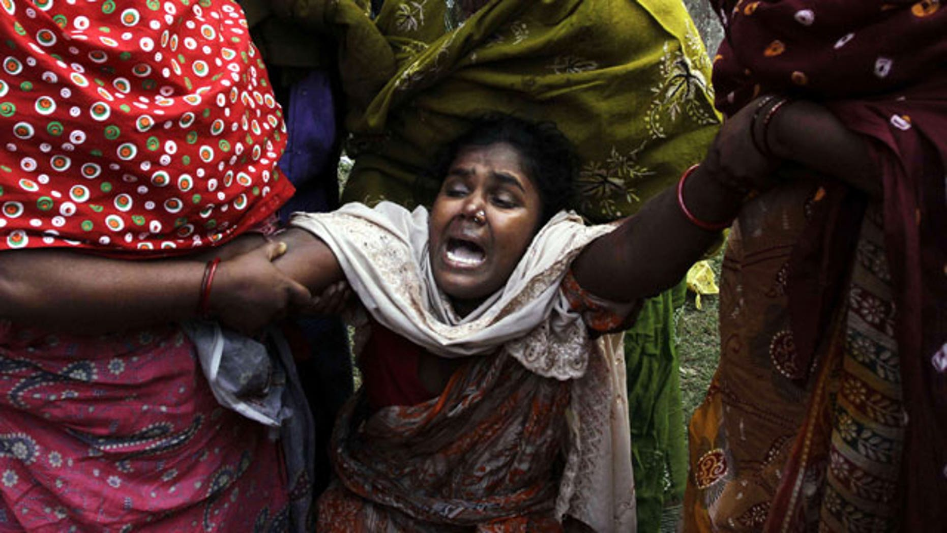 December 15, 2011: An Indian woman cries after her relative died from toxic alcohol outside a hospital in Diamond Harbour, near Kolkata, India.