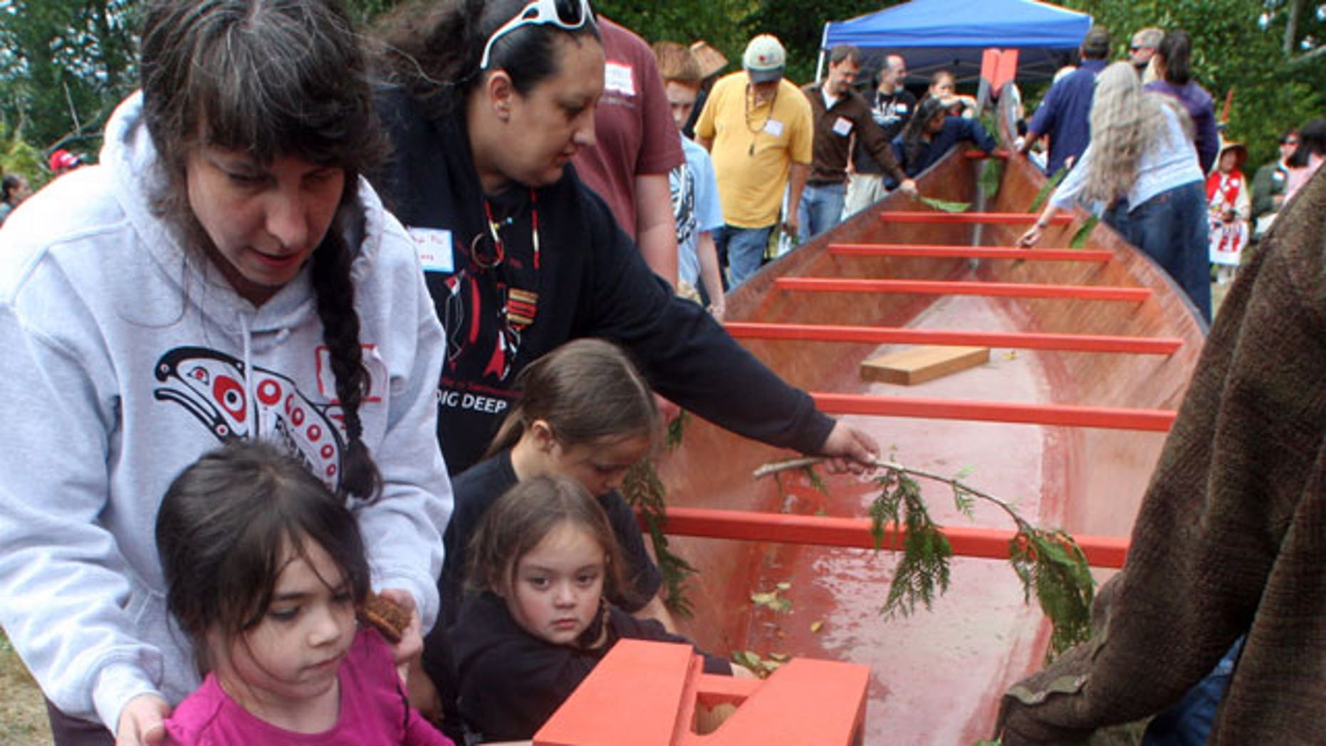 September 24: Mylee Wahlgren, 6, left, and her grandmother Donna Sinclair, of Washougal, Wash., bless the 36-foot replica canoe during the canoe reparation ceremony at Fort Columbia, near Chinook, Wash.