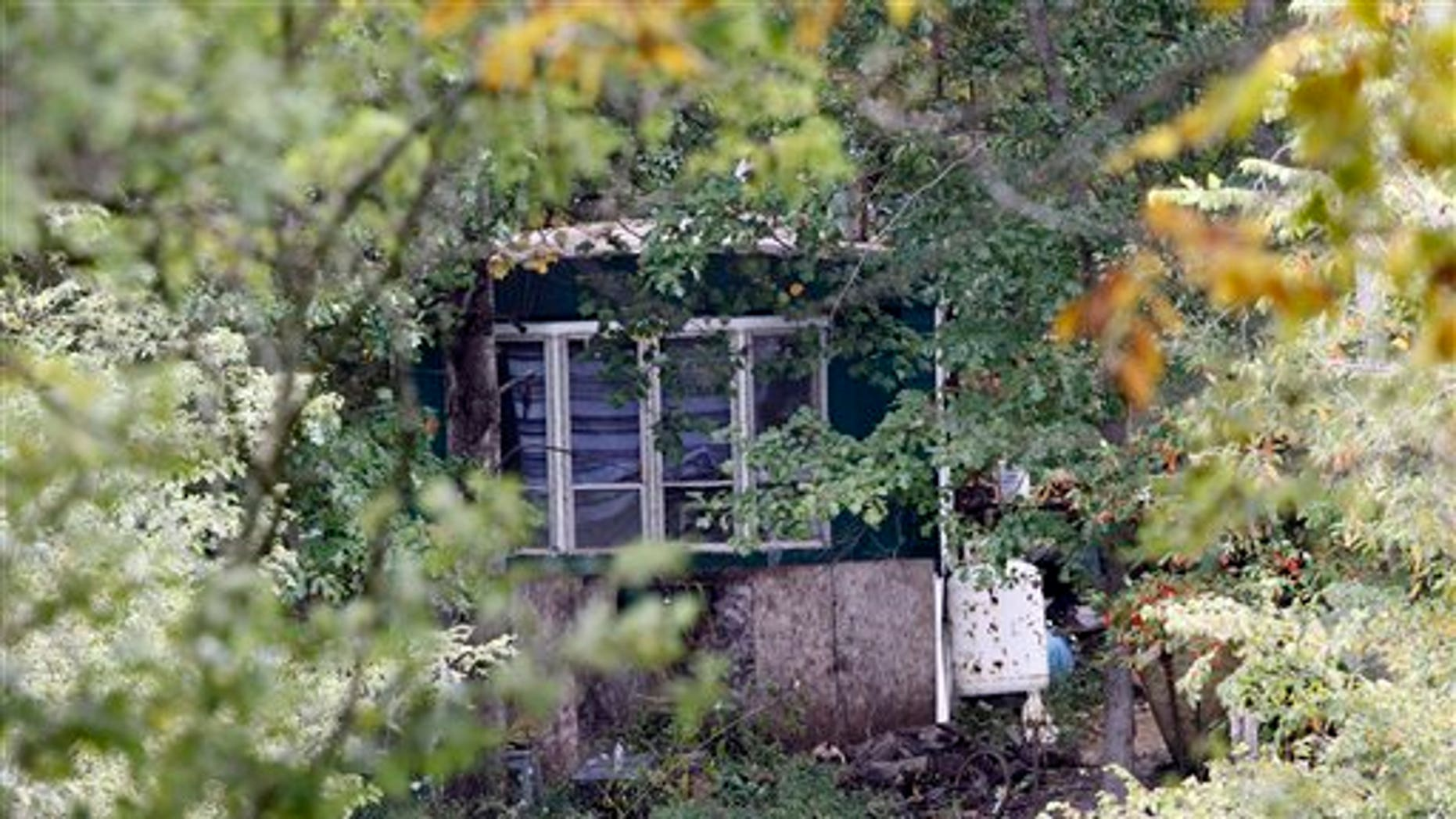 Sept. 26: Trees and brush surround the mobile home of Roy Napier where four people were found dead in rural Franklin County near Laurel, Ind. A fifth person was found dead across the street.