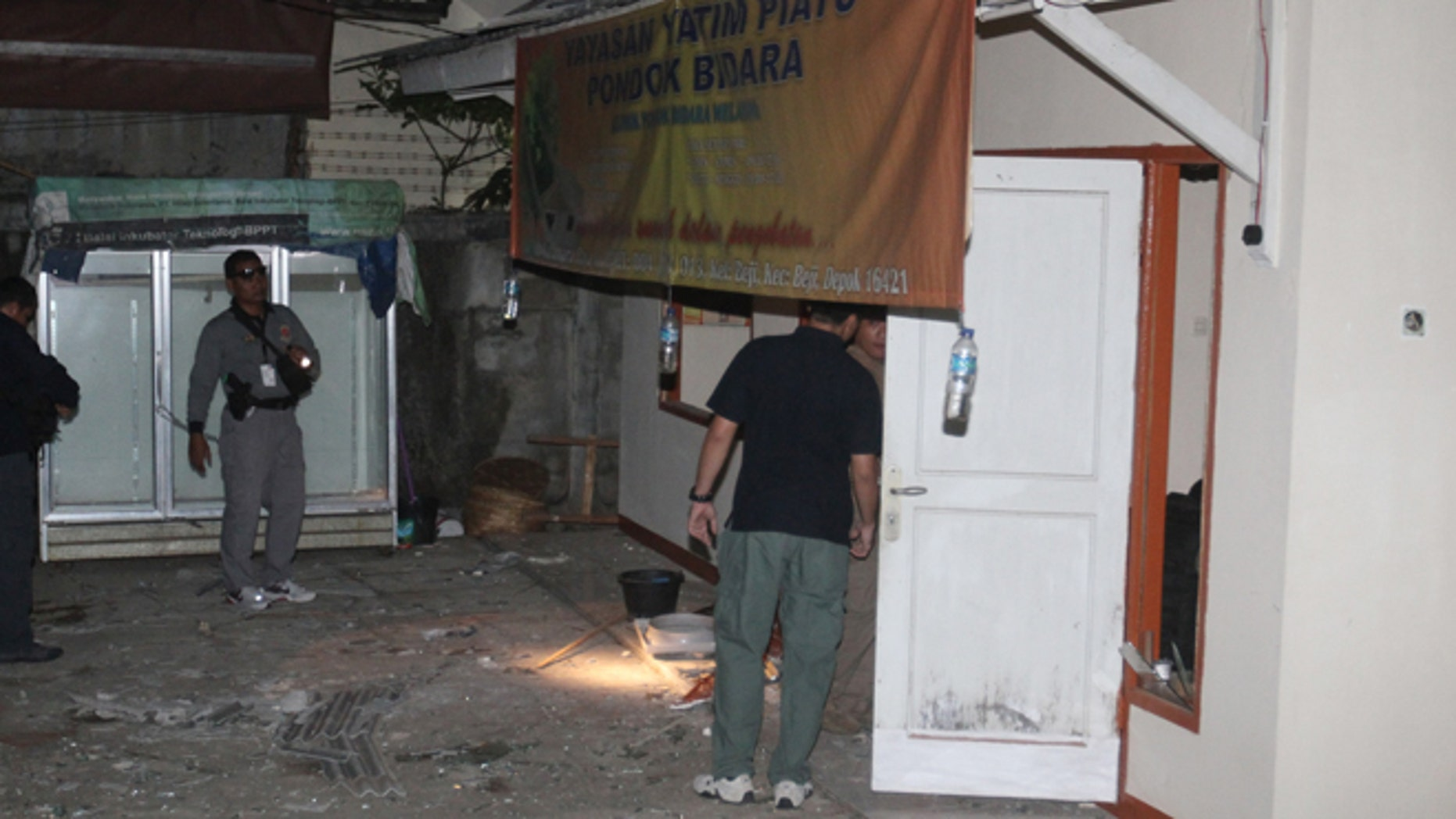 Sept. 8, 2012: Plain-clothed police officers examine a house where an explosion went off in Depok, West Java, Indonesia.