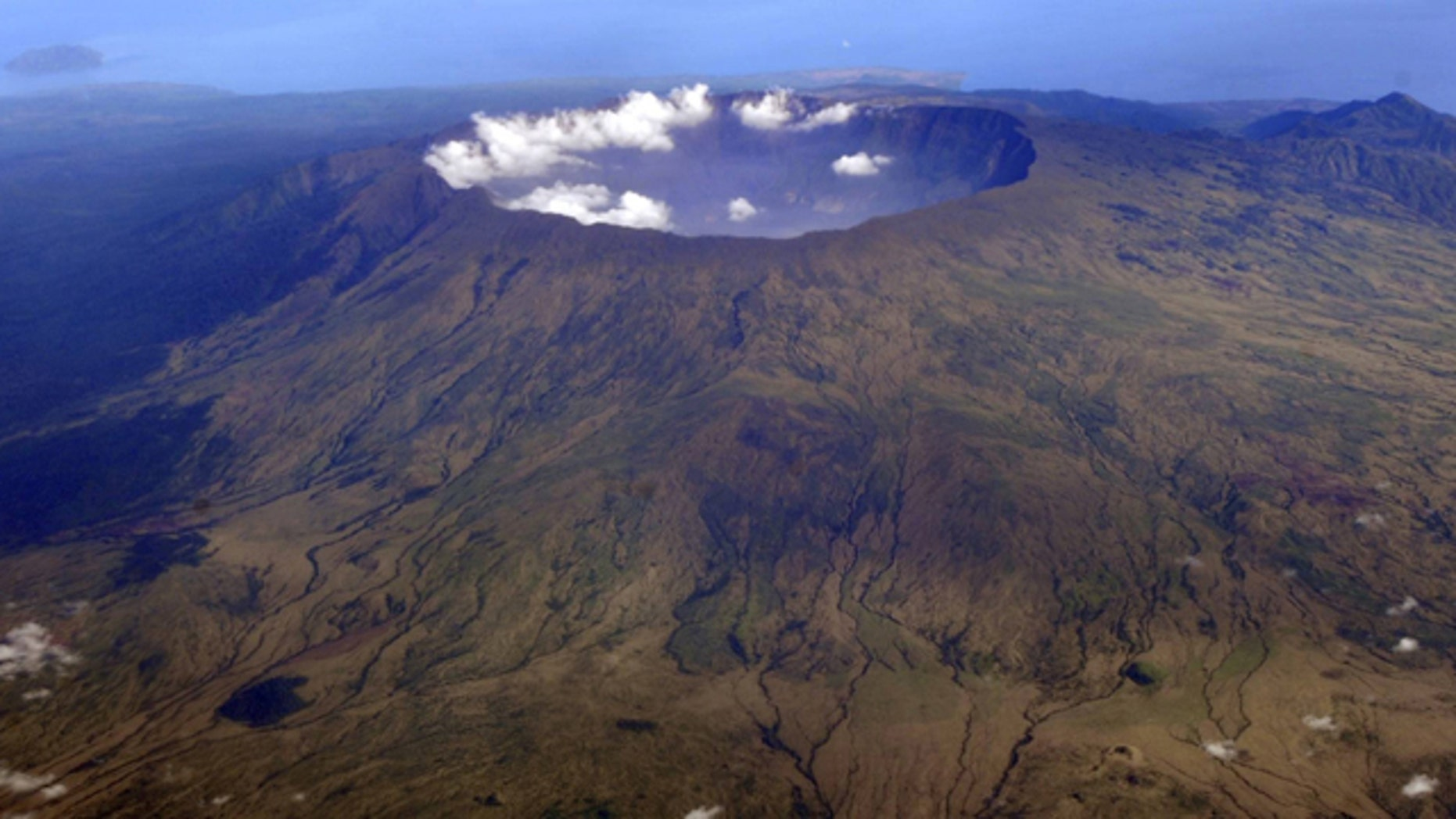 """Oct. 19, 2010"""" Mount Tambora's 10 kilometer wide and 1 kilometer deep volcanic crater, created by the April 1815 eruption, is shown. Bold farmers routinely ignore orders to evacuate the slopes of live volcanos in Indonesia, but those on Tambora took no chances when history's deadliest mountain rumbled ominously this month, Sept., 2011."""