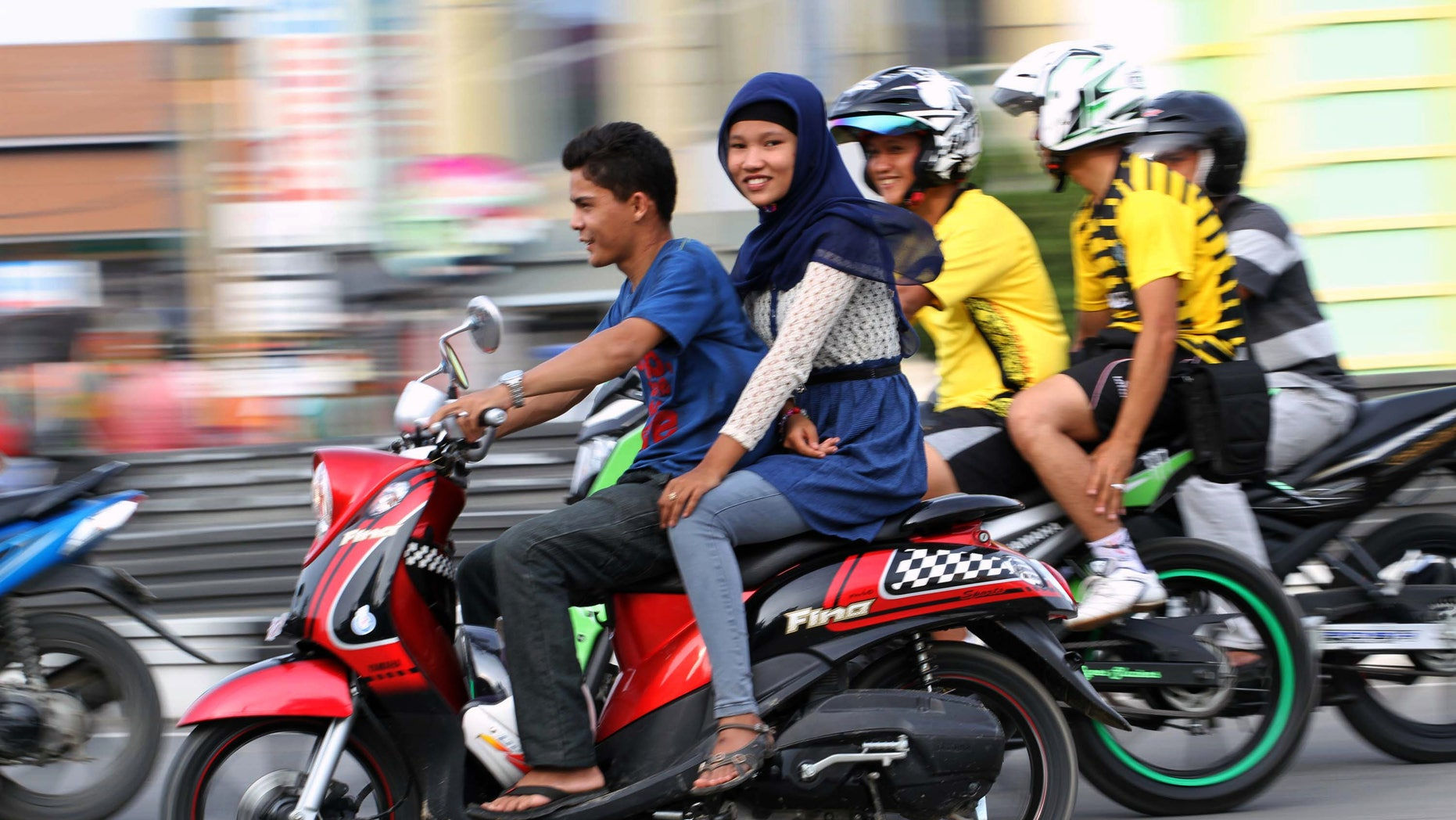 Jan. 7, 2013 - An Acehnese woman straddles on a motorbike on a road in Lhokseumawe, Aceh province, Indonesia.