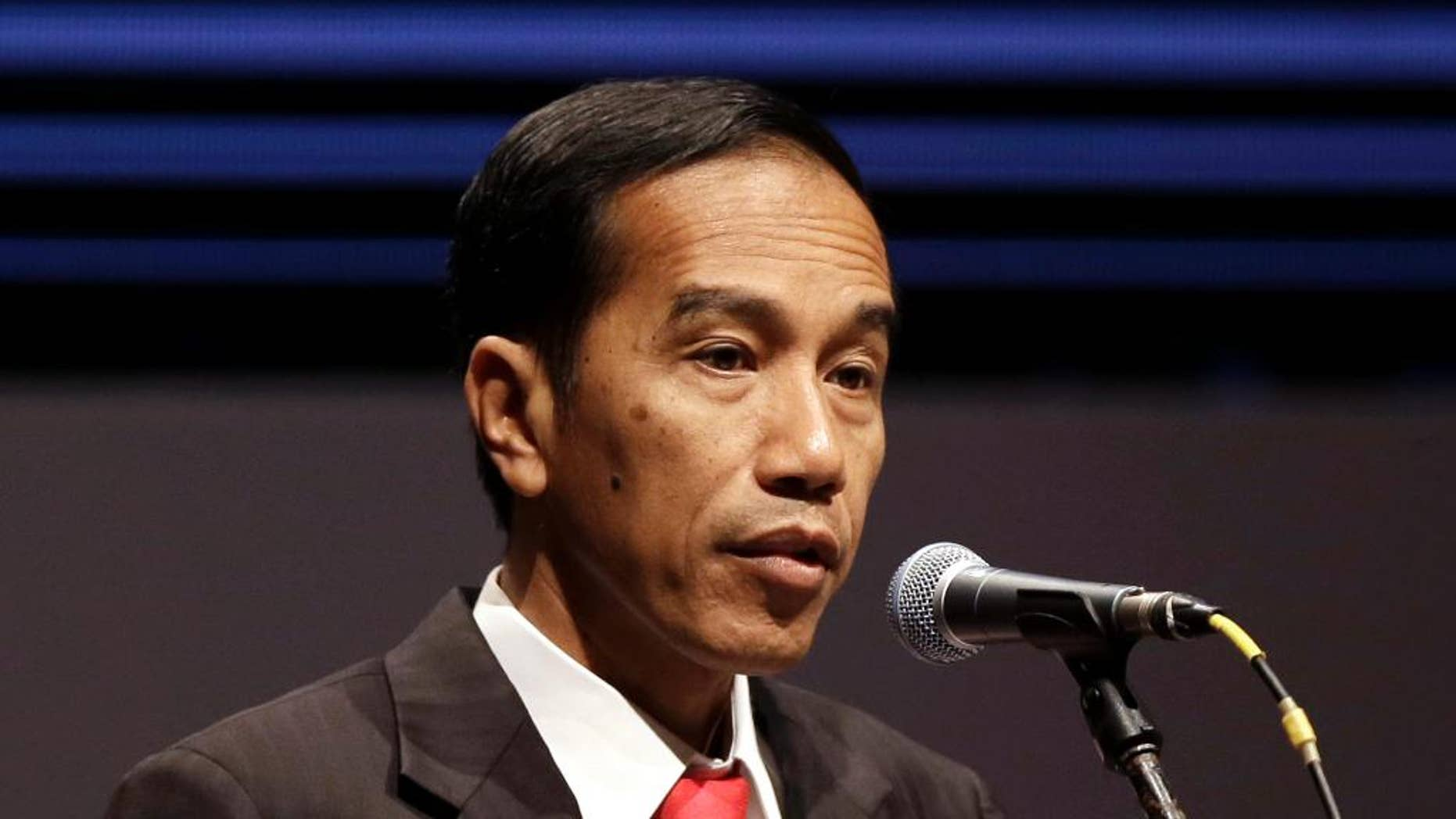 FILE - In this April 21, 2015 file photo, Indonesian President Joko Widodo delivers his remarks during Asian African Business Summit on the sideline of Asian African Conference in Jakarta, Indonesia. Indonesia's president has announced the lifting of a travel ban for foreign journalists to the country's easternmost Papua province and freed five Papuan political prisoners following their appeal for clemency. Widodo announced the lifting of the ban Sunday, May 10, 2015 during his three-day visit to the province. (AP Photo/Dita Alangkara, File)