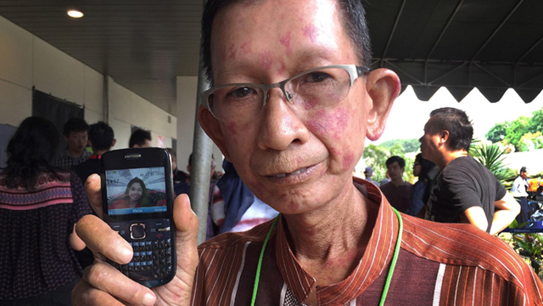 Dec. 31, 2014: Haidar Fauzie, 60, holds up a picture of his daughter Khairunnisa Haidar, 22, who was a flight attendant on AirAsia Flight 8501, at Juanda International Airport in Surabaya, Indonesia. (AP Photo/Eileen Ng)