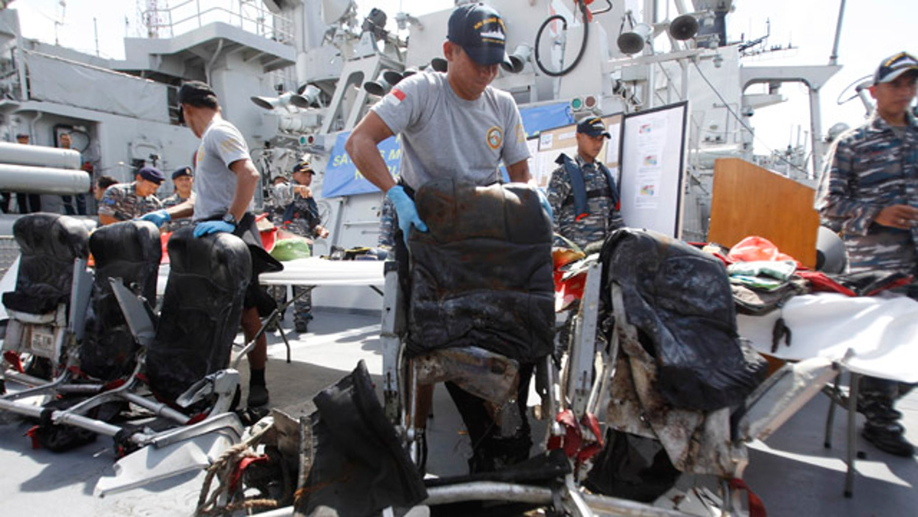 Jan. 5, 2015: Crew members of Indonesian Navy ship KRI Bung Tomo show airplane seats from AirAsia Flight 8501 recovered during search operations for the ill-fated jetliner during a press conference at the Navy's Eastern Fleet Naval Base in Surabaya, East Java.  (AP Photo/Trisnadi)