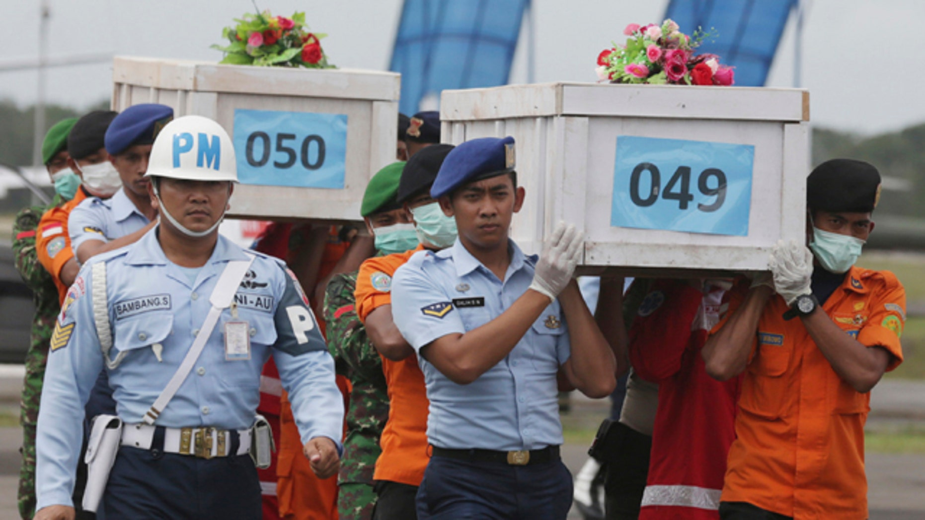 Jan. 19, 2015: Mmbers of the National Search and Rescue Agency carry coffins containing bodies of the victims aboard AirAsia Flight 8501 to transfer to Surabaya at the airport in Pangkalan Bun, Indonesia. (AP Photo/Achmad Ibrahim, File)