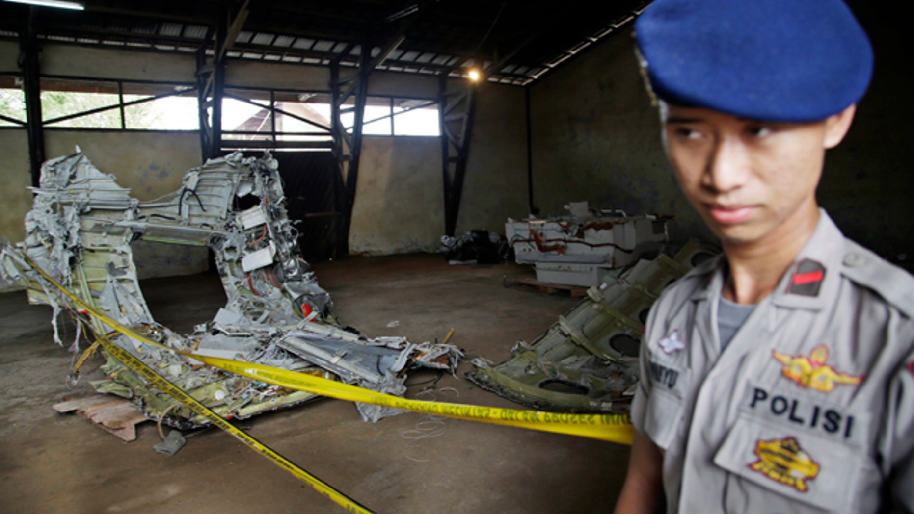 Jan. 19, 2015: An Indonesian police officer stands guard near the wreckage of AirAsia Flight 8501 at a warehouse at Kumai port in Pangkalan Bun.  The plane disappeared Dec. 28, 2014 en route from Surabaya, Indonesia, to Singapore. (AP Photo/Achmad Ibrahim)