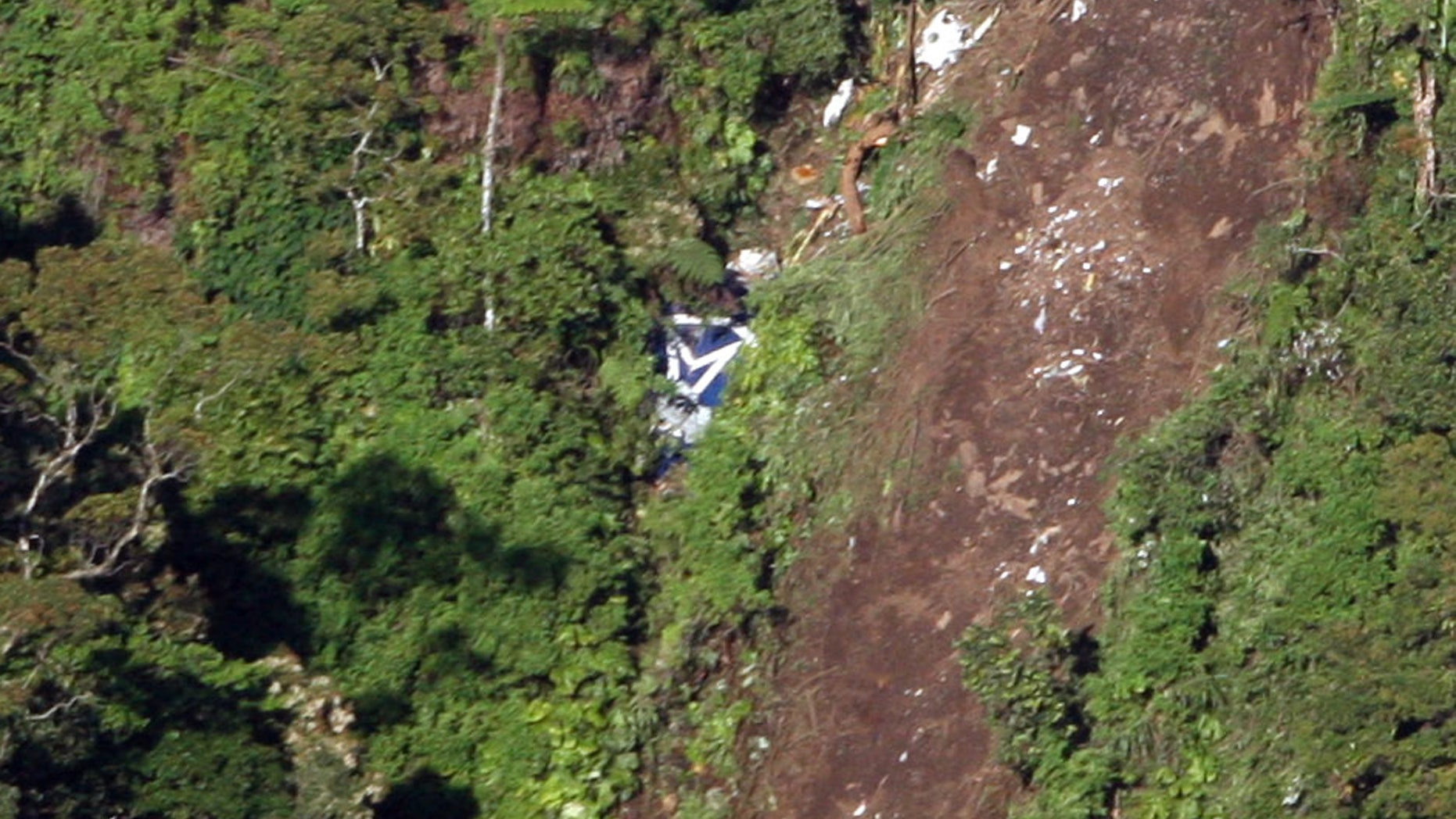 May 11, 2012: The logo of Sukhoi Co. is clearly visible, center, among the wreckage of a Sukhoi Superjet-100 scattered on the mountainside in Bogor, West Java, Indonesia.