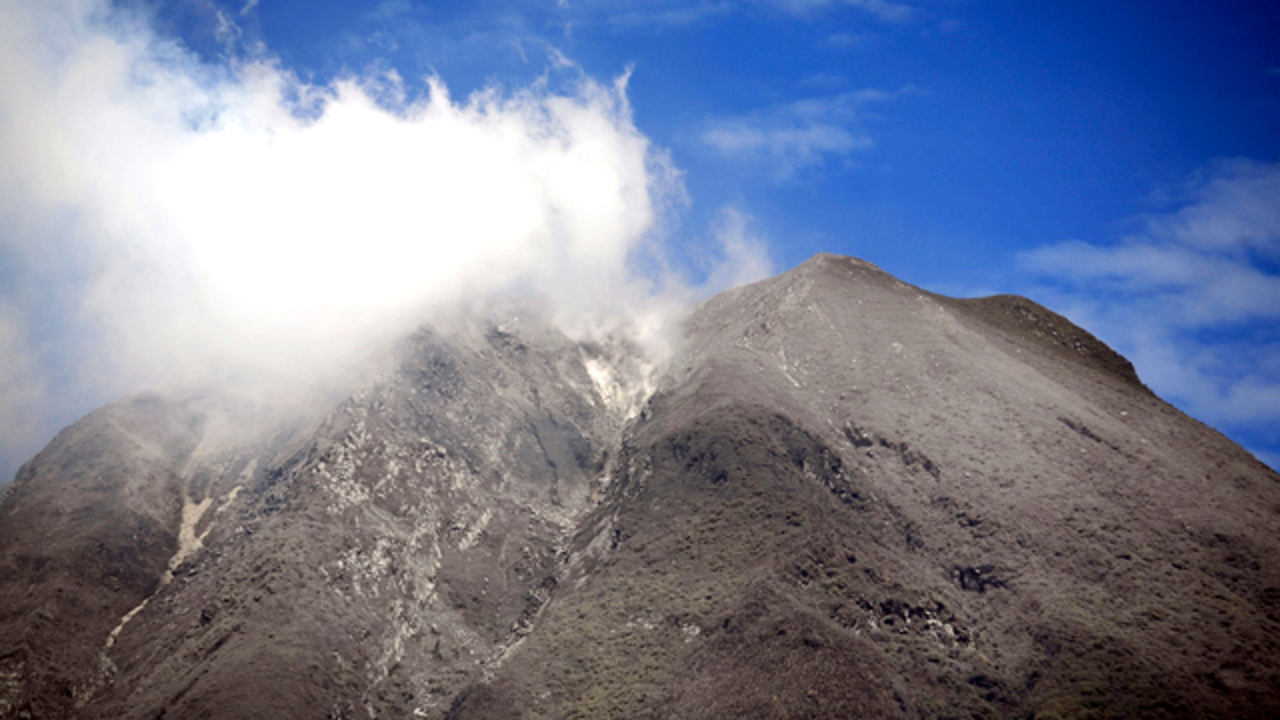 Mount Sinabung spews volcanic smoke as seen from Tanah Karo, North Sumatra, Indonesia, Tuesday, Sept. 7, 2010. The volcano shot volcanic ash high into the air Tuesday, dusting villages 15 miles (25 kilometers) away in its most powerful eruption since awakening last week from four centuries of dormancy.