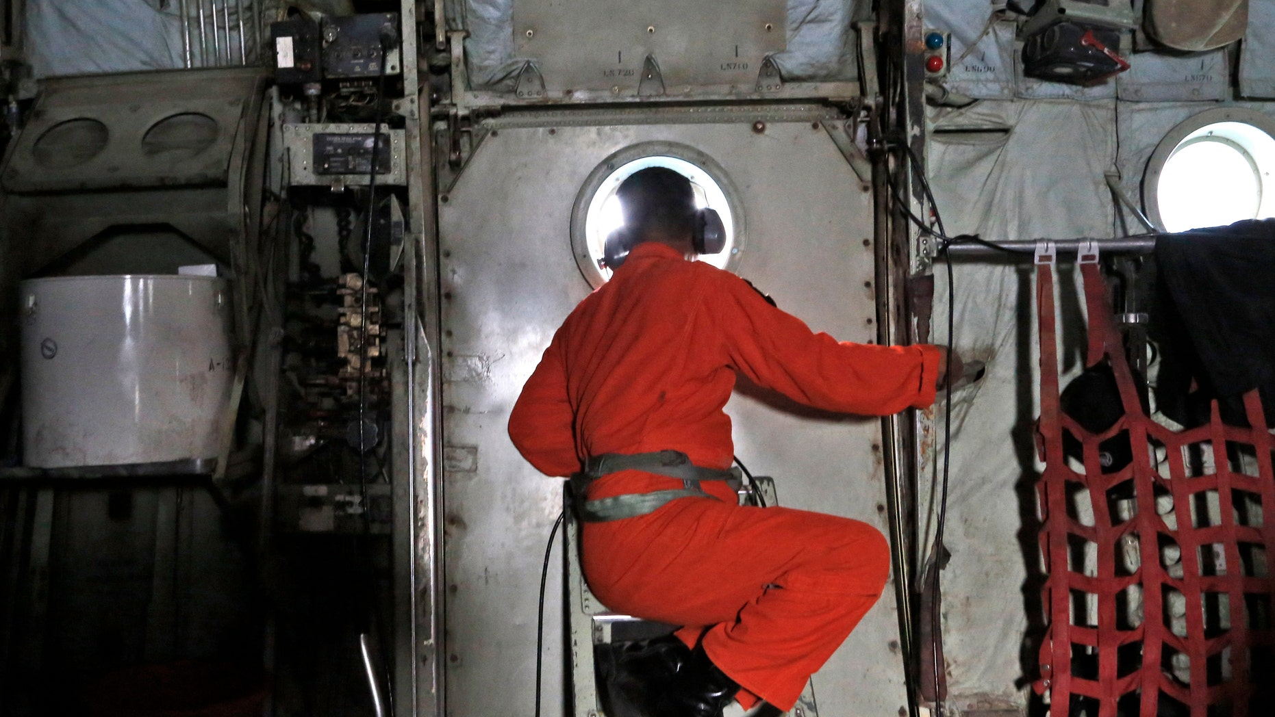 Dec. 29, 2014: A crew of an Indonesian Air Force C-130 airplane of the 31st Air Squadron, looks out of the window during a search operation for the missing AirAsia flight 8501 jetliner over the waters of Karimata Strait in Indonesia.