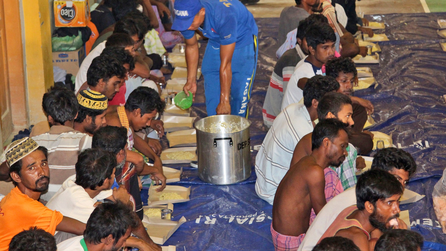 May 11, 2015 - Ethnic Rohingya migrants receive food from a social worker at a temporary shelter in Lhok Sukon, Aceh province, Indonesia. Boats carrying nearly 600 Bangladeshis and long-persecuted Rohingya Muslims from Myanmar washed ashore in western Indonesia, some after captains and smugglers abandoned the ships, survivors said.