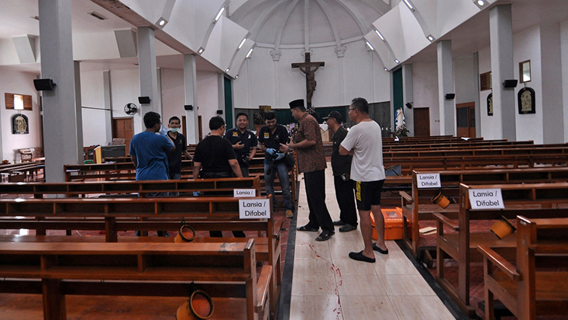 Police officers investigate inside St. Lidwina Church following an attack in Sleman, Yogyakarta province, Indonesia, Sunday, Feb. 11, 2018. Police shot a sword-wielding man who attack the church during a mass, injuring a number of people including a German priest. The reason for the attack Sunday morning was not immediately clear. (AP Photo/Slamet Riyadi)