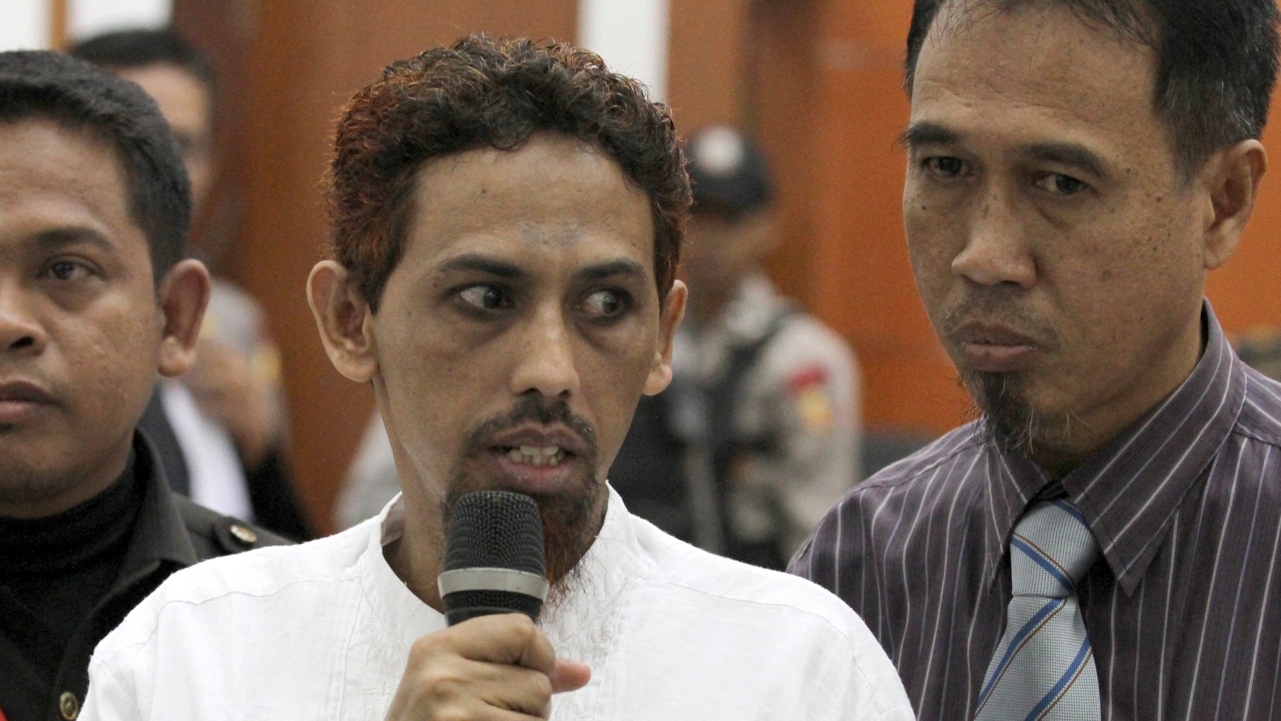 May 7, 2012: Indonesian militant Umar Patek, center, accompanied by his lawyer Ashludin Hatjani, right, speaks to the press during his trial at West Jakarta District Court in Jakarta, Indonesia.