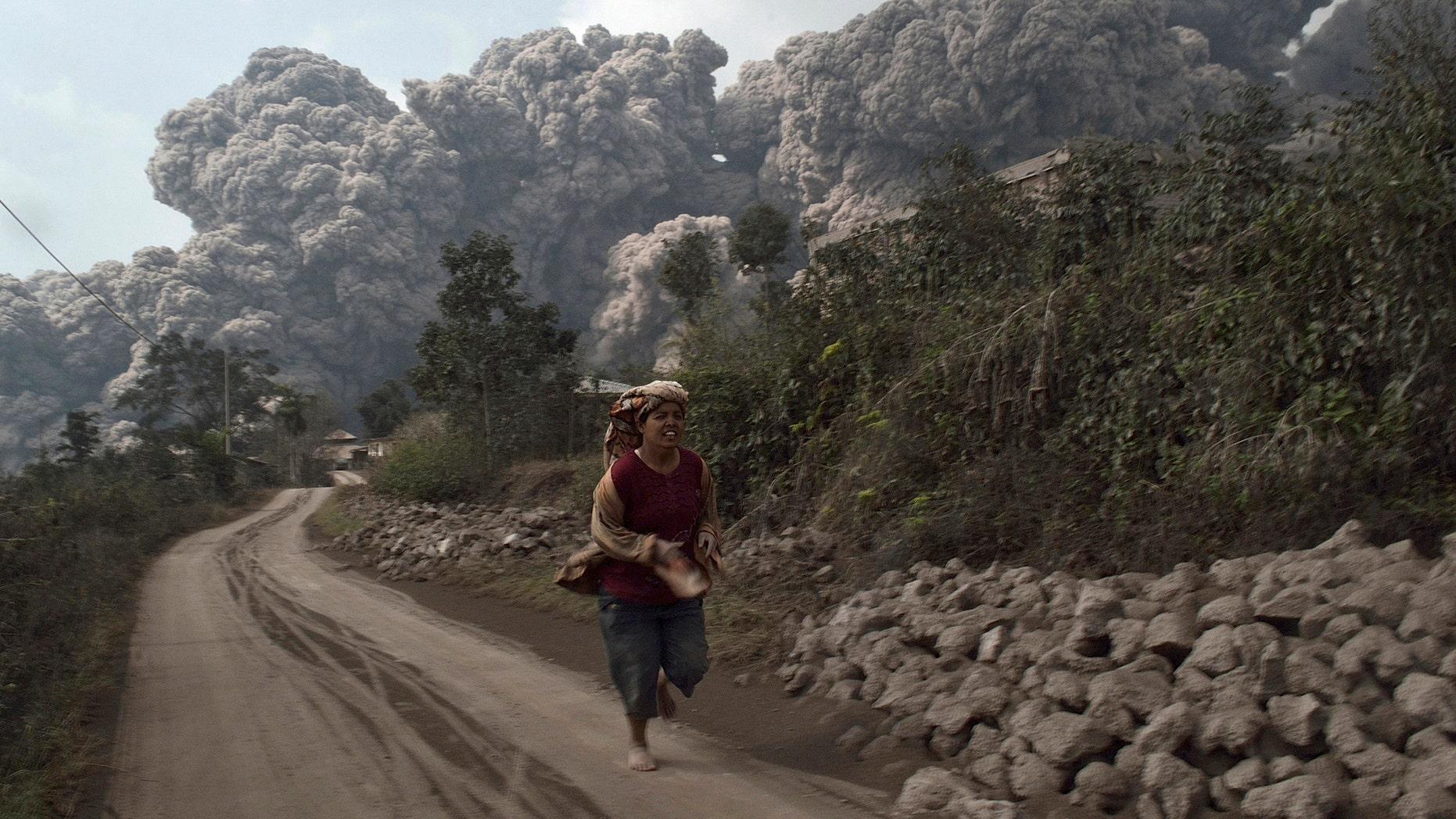 Feb. 1, 2014: A villager runs as Mount Sinabung erupt at Sigarang-Garang village in Karo district, Indonesia's North Sumatra province.