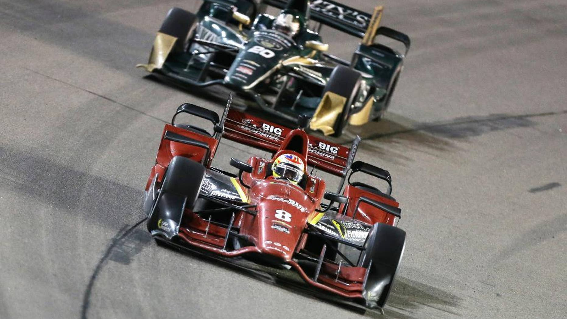 FILE - In this July 18, 2015, file photo, Sage Karam (8) leads Ed Carpenter during an IndyCar Series auto race at Iowa Speedway in Newton, Iowa. Karam won't win the IndyCar title this season. But the Chip Ganassi rookie might push for the championship before long based on his recent performances _ including his first podium last weekend in Iowa.  (AP Photo/Charlie Neibergall, File)
