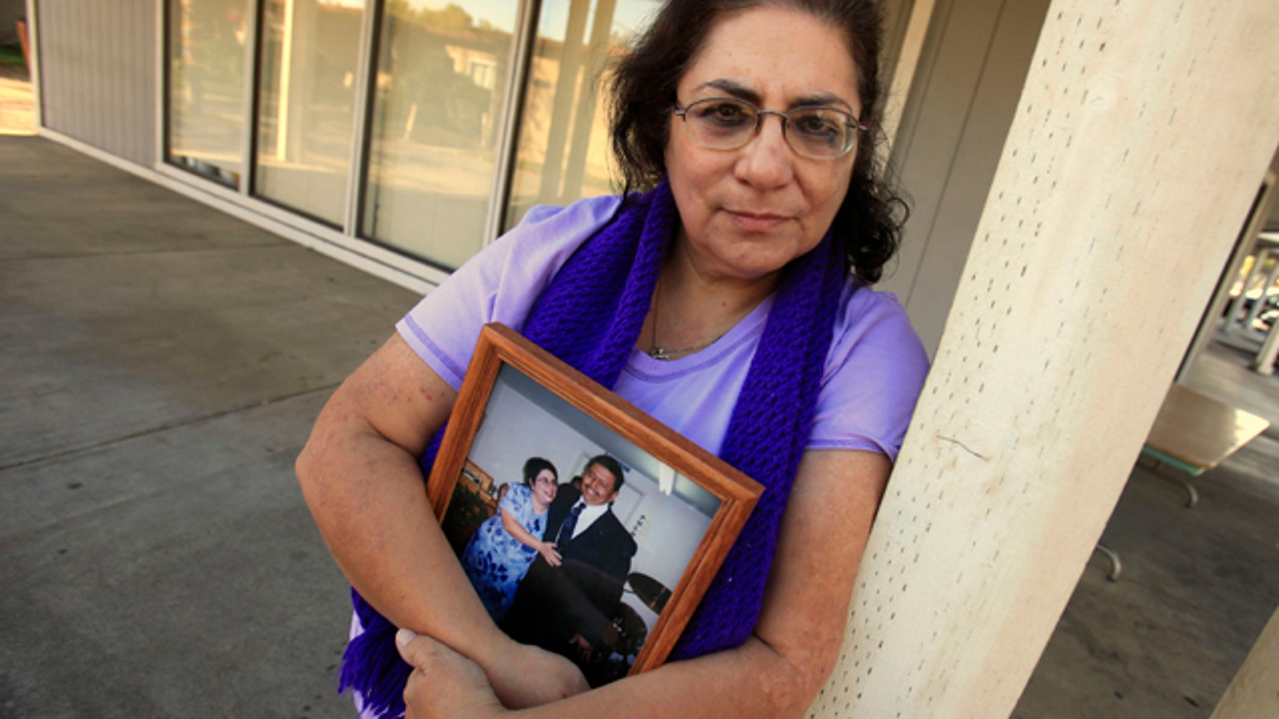 Nov. 4, 2011: Karen Carrisosa is seen with a photo of her and her husband Larry, at the site where he was killed in Sacramento, Calif. Carrisosa is a victim of a disturbing trend: Inmates who use smuggled mobile devices or work through third parties to access social networking sites -- giving them the ability to harass their victims and victim's families.
