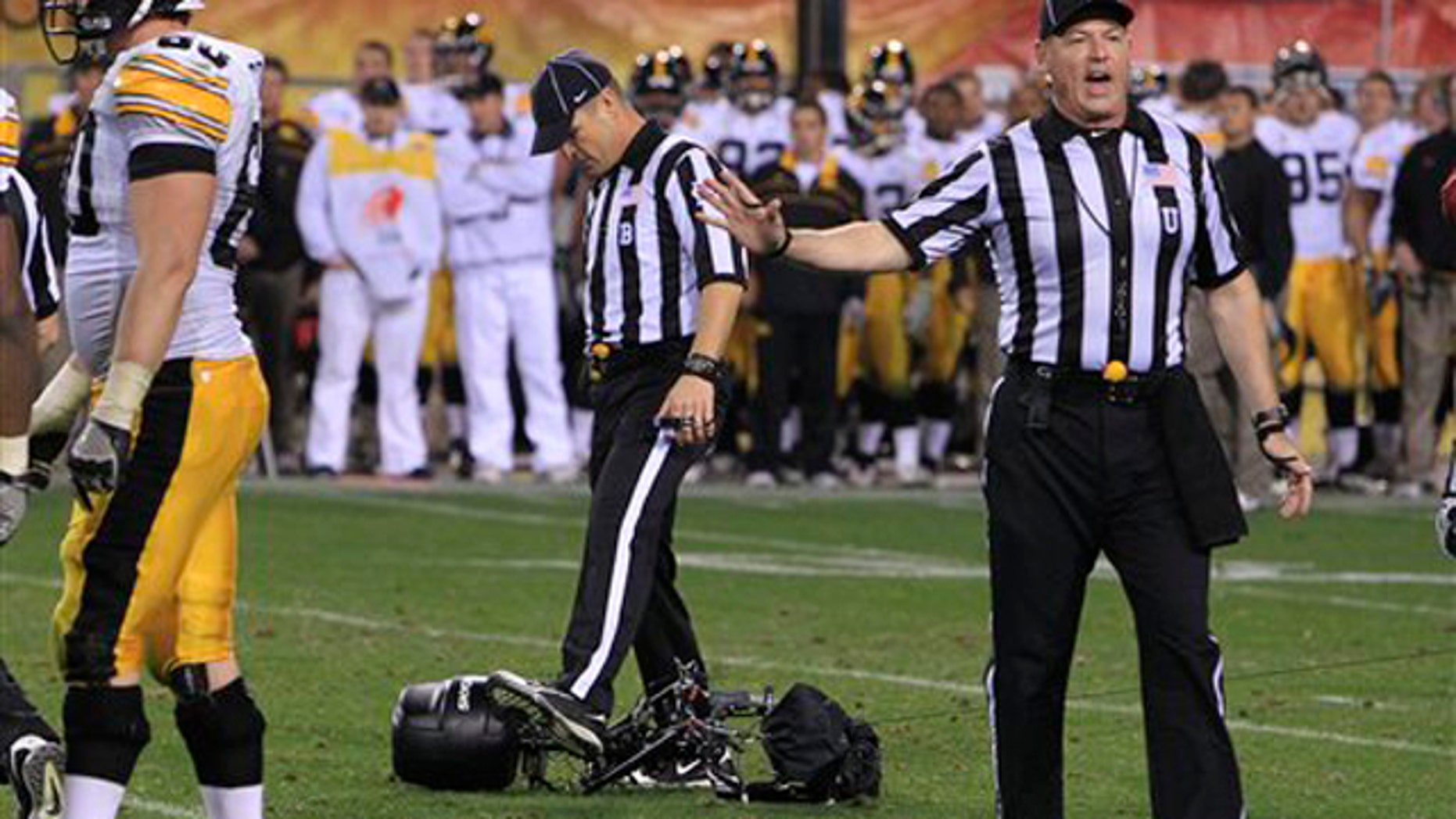 Umpire Tim Schroeder, right, keeps players away as back judge William Robinson kicks a network overhead television camera after it crashed to the field during the fourth quarter in the Insight Bowl NCAA college football game Friday, Dec. 30, 2011, in Tempe, Ariz.  Oklahoma defeated Iowa 31-14.(AP Photo/Ross D. Franklin)