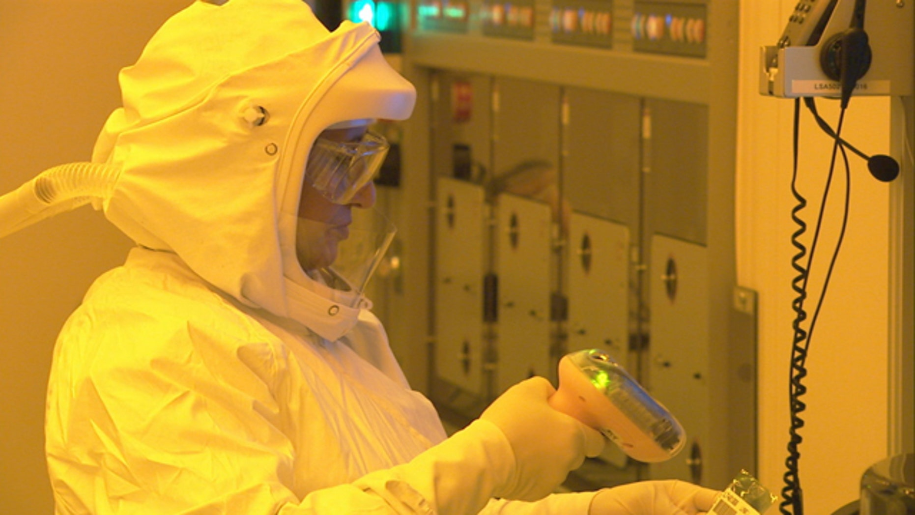 A manufacturing technician, wearing a protective suit to keep dust particles out of a clean room, uses a scanner to start production of CPU wafers inside an Intel chip factory in Chandler, Ariz.
