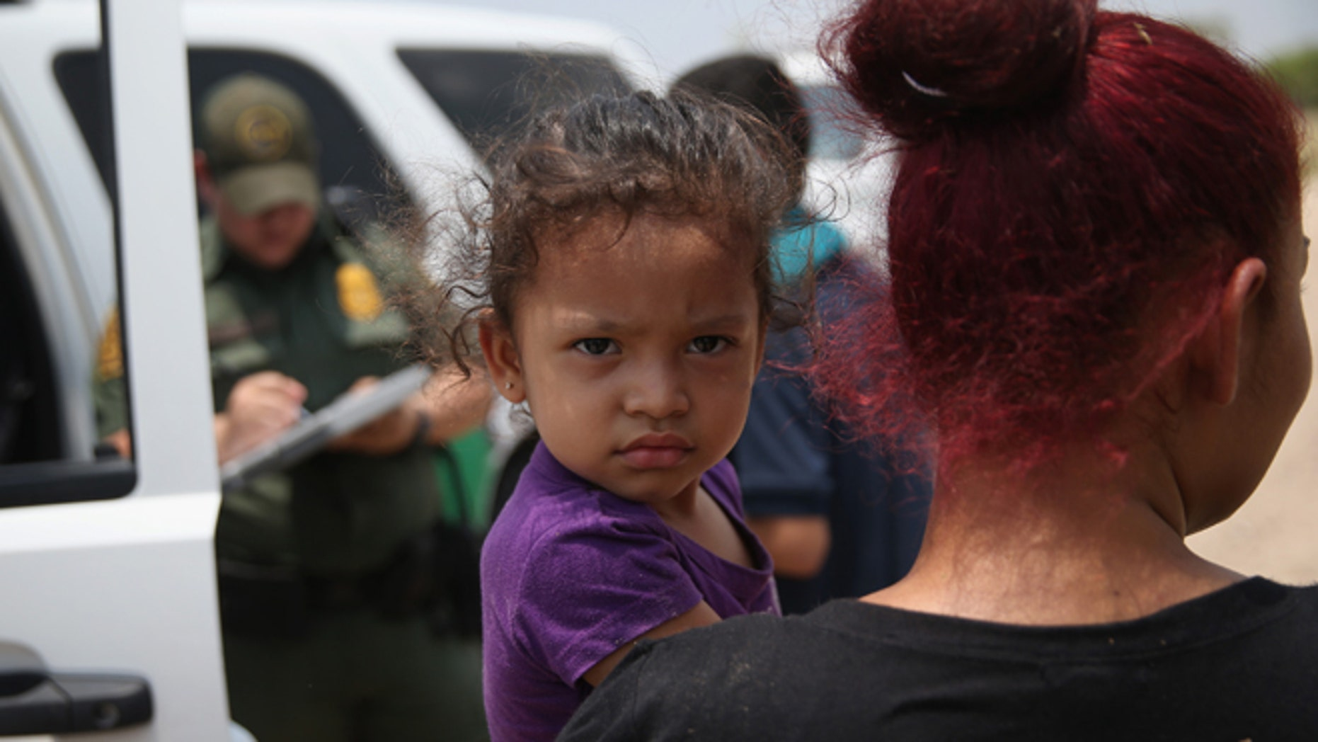 MISSION, TX - JULY 24:  A mother and child, 3, from El Salvador await transport to a processing center for undocumented immigrants after they crossed the Rio Grande into the United States on July 24, 2014 in Mission, Texas. Tens of thousands of immigrant families and unaccompanied minors have crossed illegally into the United States this year and presented themselves to federal agents, causing a humanitarian crisis on the U.S.-Mexico border.  (Photo by John Moore/Getty Images)