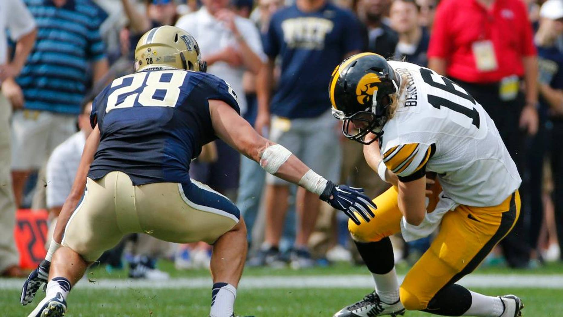 Iowa quarterback C.J. Beathard (16) slides before being tackled by Pitt linebacker Anthony Gonzalez (28) after a short gain during the fourth quarter of an NCAA college football game in Pittsburgh, Saturday, Sept. 20, 2014. Iowa won 24-20. (AP Photo/Gene Puskar)