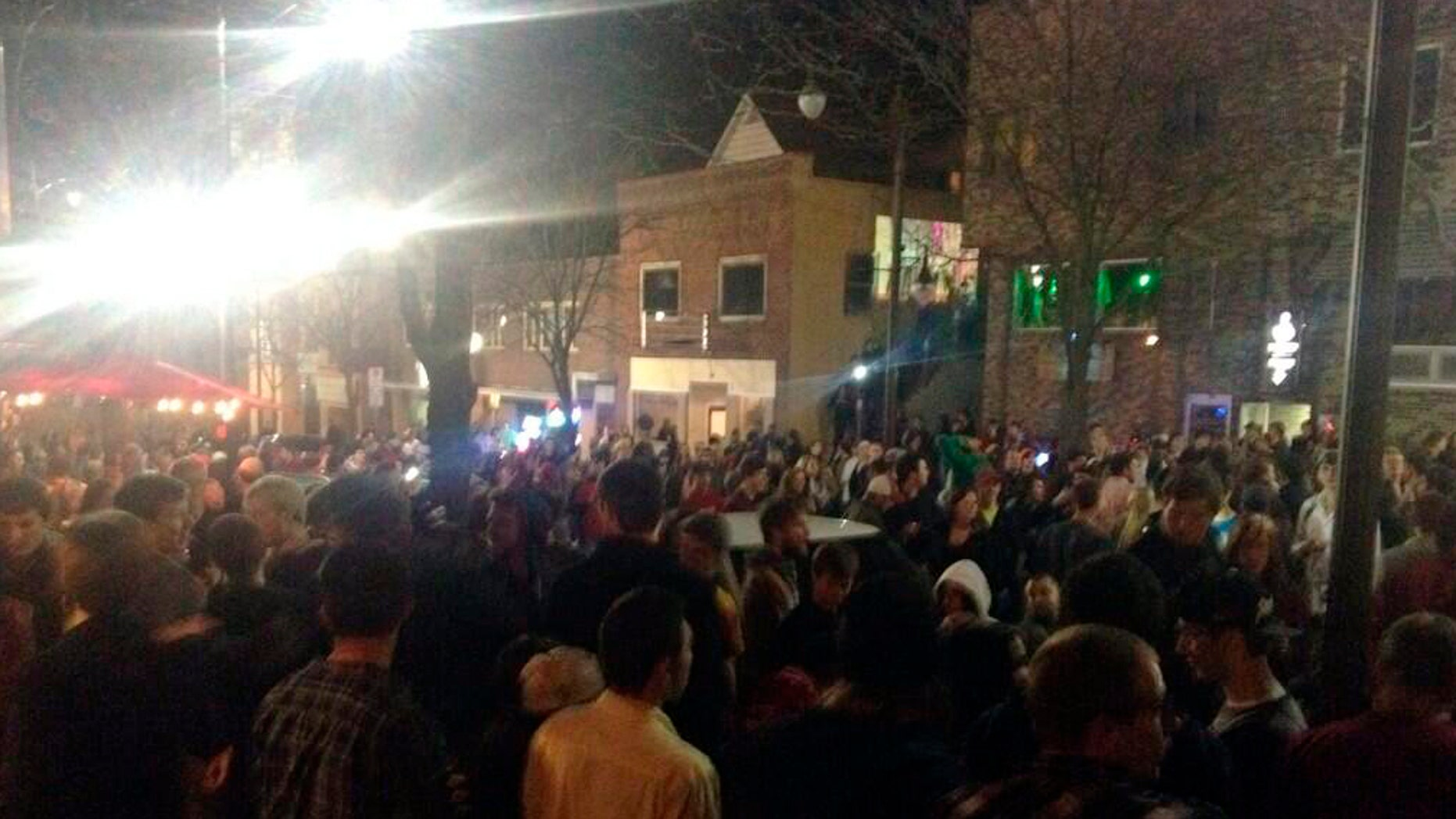 Crowds gathered on Welch Avenue on Tuesday night, April 8, 2014 in the Campustown area of Ames, Iowa. A student was seriously injured after a rowdy crowd overturned cars and toppled light poles near the Iowa State University campus during the annual Veishea celebration designed to showcase the educational establishment, its students and alumni, authorities said Wednesday. (AP Photo/The Des Moines Register, Katherine Klingseis) MAGS OUT, TV OUT, NO SALES, MANDATORY CREDIT