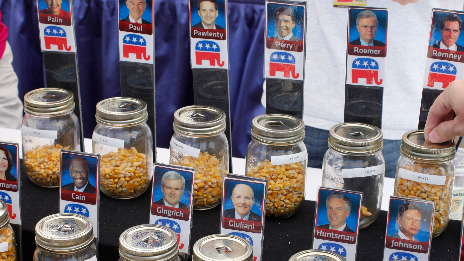 """FILE - In this Aug. 12, 2011 file photo, a visitor places a kernel of corn for Republican presidential hopeful former Massachusetts Gov. Mitt Romney during an informal """"corn poll"""" at the Iowa State Fair in Des Moines, Iowa.  (AP Photo/Charles Dharapak, File)"""
