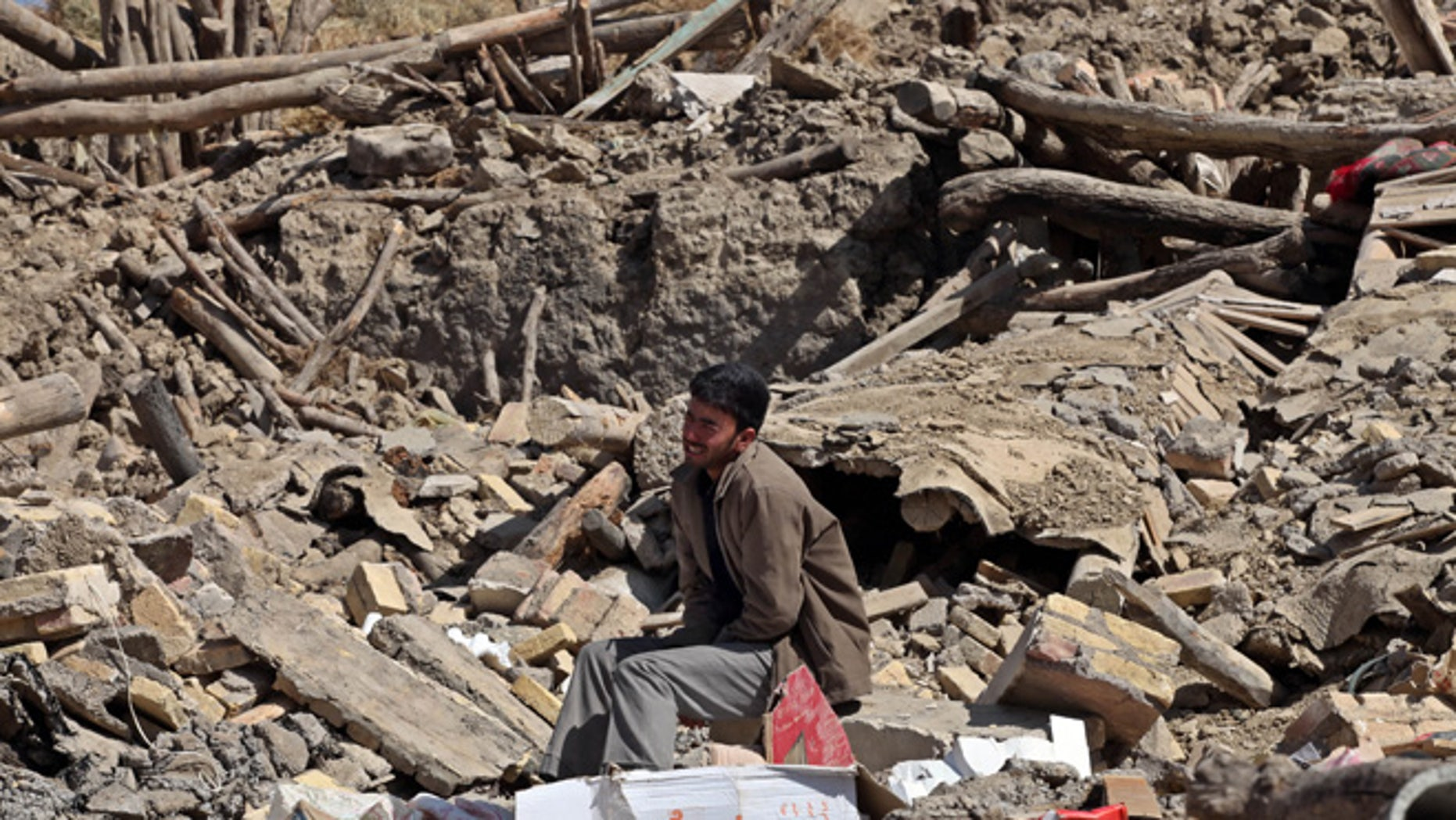 Aug. 13, 2012: A victim of Saturday's earthquake grieves as he sits on ruins of buildings in a village near the Iranian city of Varzaqan.