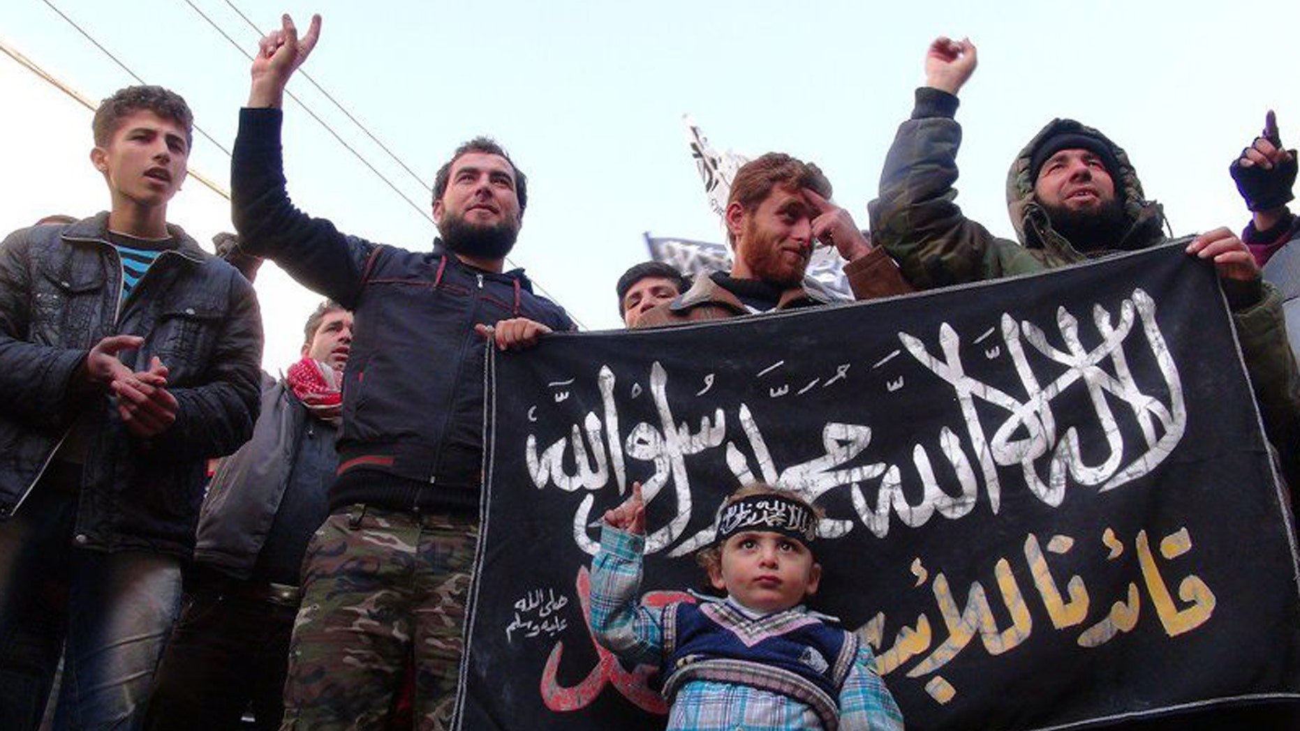 Jan. 25, 2013: This citizen journalism image provided by Edlib News Network, ENN, which has been authenticated based on its contents and other AP reporting, shows Syrians chanting slogans and holding an Islamic banner during a demonstration after Friday prayer, at Binnish village in Idlib province, north Syria.