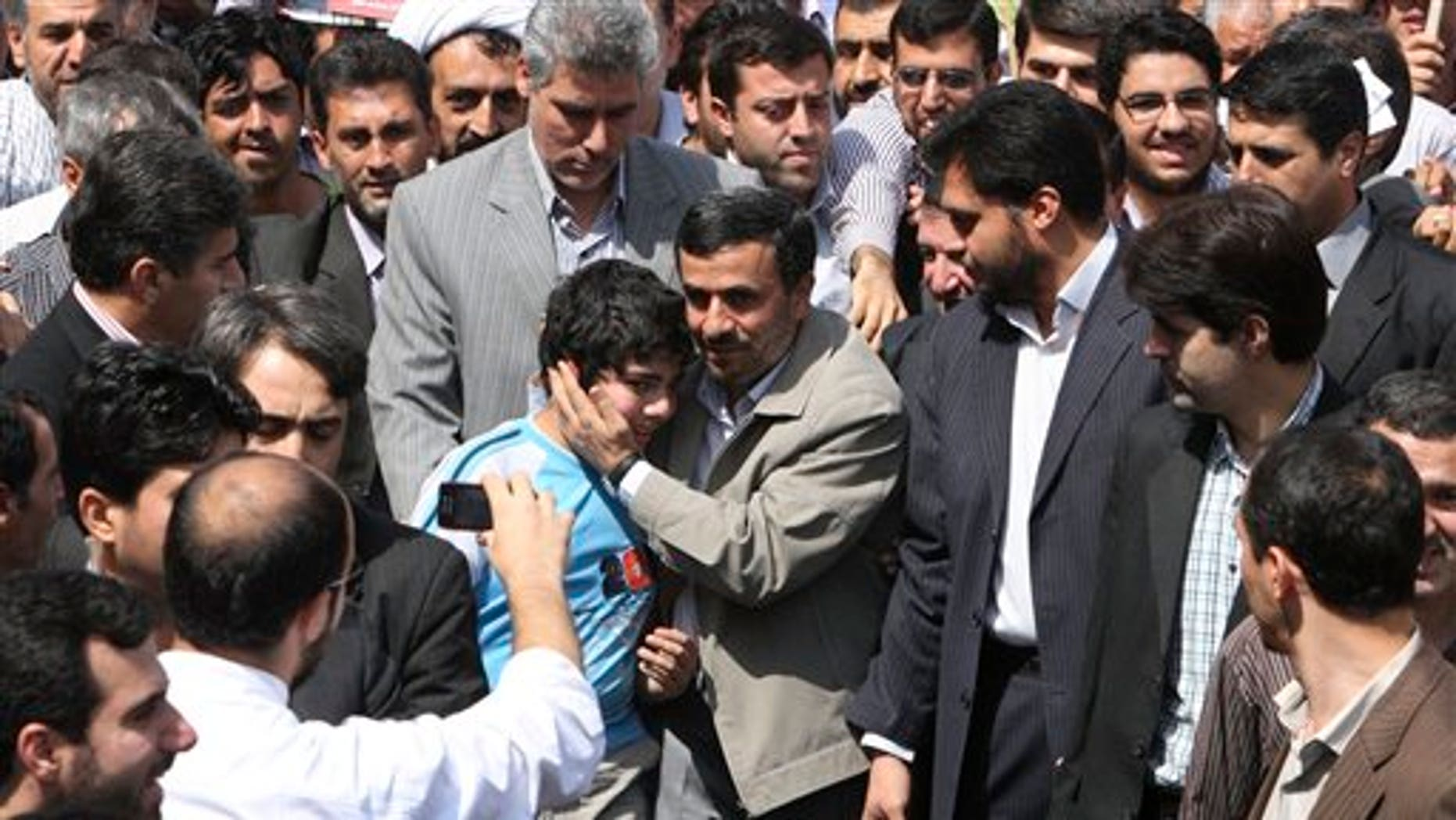 August 26: Escorted by his bodyguards, Iranian President Mahmoud Ahmadinejad, center, greets a boy, as he attends an annual nation-wide pro-Palestinian rally known as Quds Day, in Tehran, Iran.