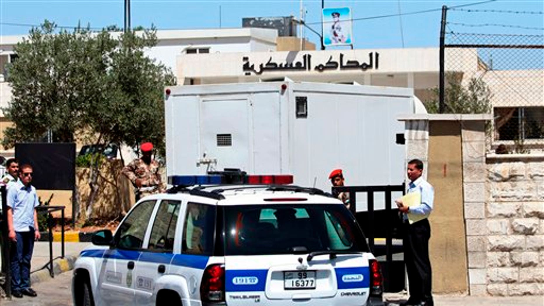 July 28: A prison van carrying Sheik Abu-Mohammed al-Maqdisi is escorted by police vehicles to a military court in Amman, Jordan.