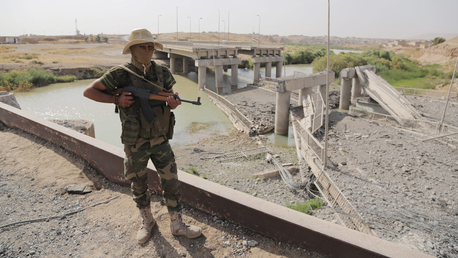 Sept. 20, 2014 - A Kurdish Peshmerga fighter stands guard near the Khazer bridge, on a  road between Mosul and Irbil, Iraq, destroyed by ISIS fighters in clashes with Kurdish forces. The destruction of the bridge cut off the road for civilians to Mosul and nearby Christian villages.