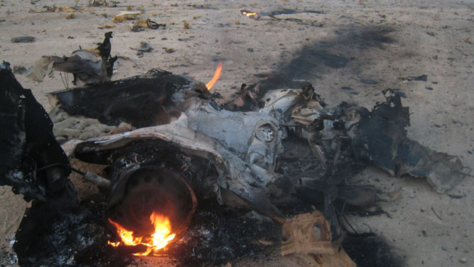 Security forces and civilians inspect the scene of a car bomb attack north of Baghdad, Iraq, Friday July 26, 2013. Attacks on civilians and government forces have escalated across Iraq recently. More than 3,000 people have been killed since April.