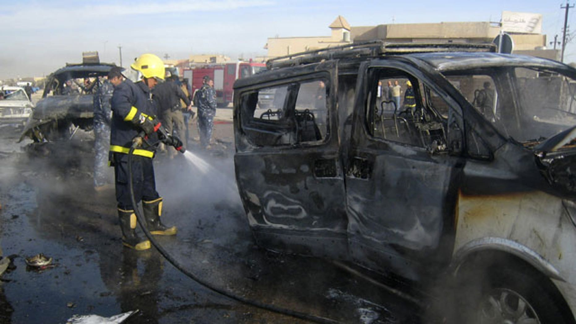 Feb. 23, 2012: An Iraqi firefighter hoses down a burned bus after a car bomb attack in Kirkuk, 290 kilometers (180 miles) north of Baghdad, Iraq. A rapid series of attacks spread over a wide swath of Iraqi territory killed and injured dozens of Iraqis on Thursday, targeting mostly security forces.