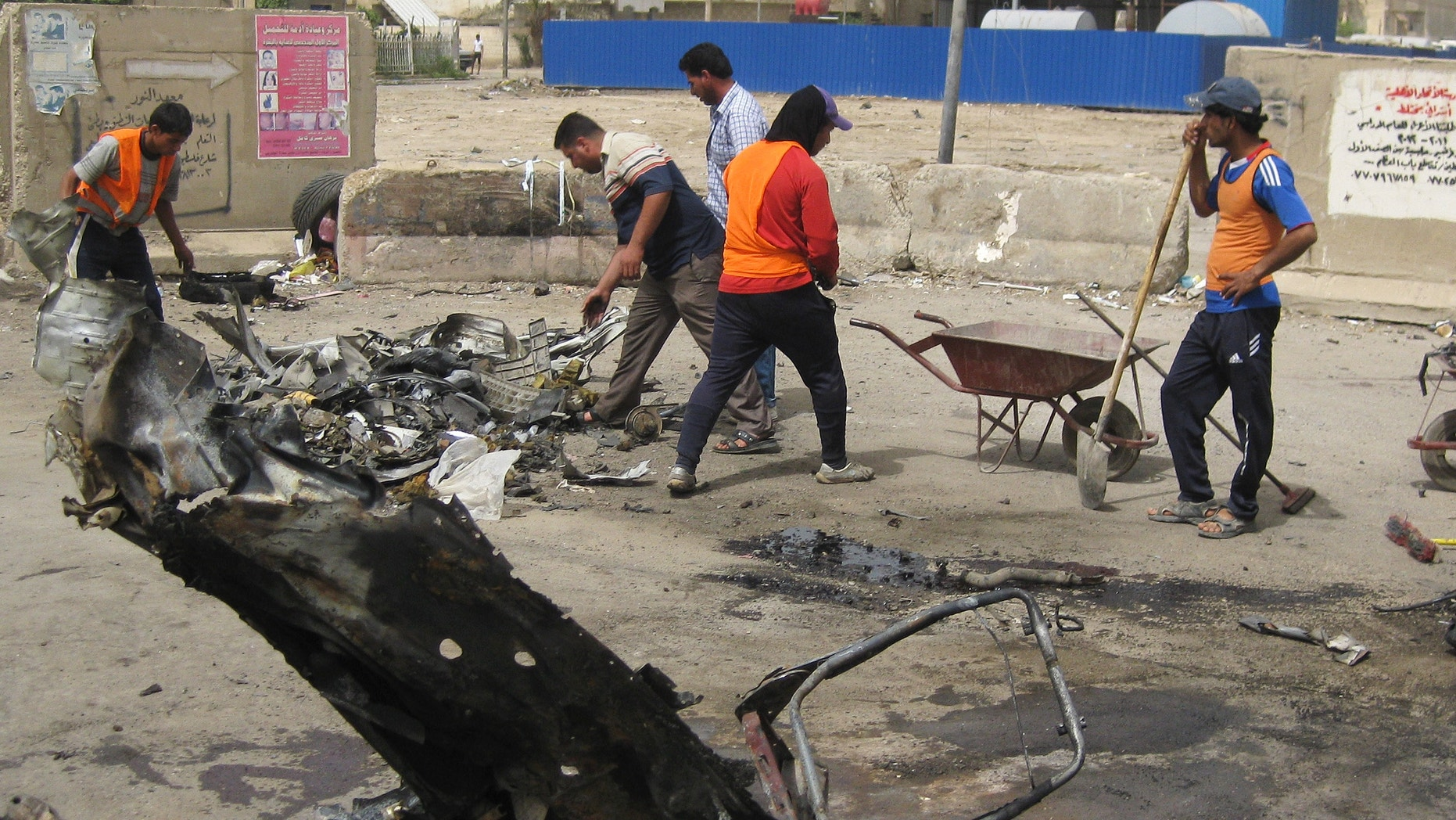 April 19, 2012: Baghdad municipality workers clean up after a car bomb attack in Palestine Street, Baghdad.