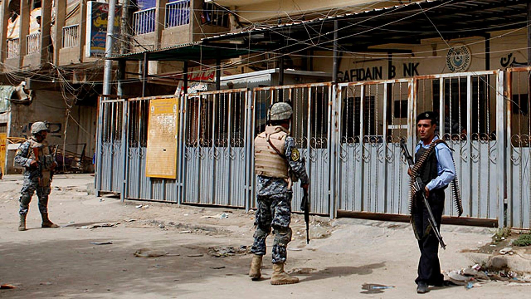 Sept. 30, 2010: Iraqi policemen stand guard outside the branch of the state-run al-Rafidain bank in southwestern Baghdad, Iraq.